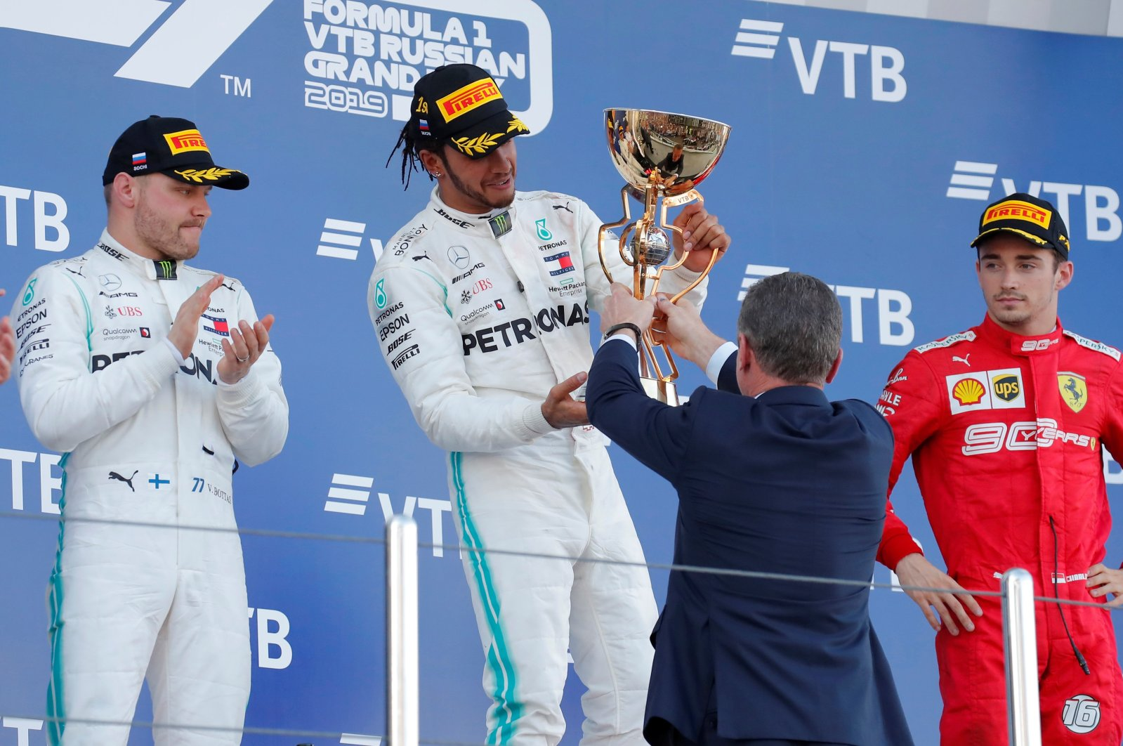 Charles Leclerc (R) stands next to Lewis Hamilton and Valtteri Bottas as Hamilton receives a trophy, in Sochi, Russia, Sept. 29, 2019. (Reuters Photo)