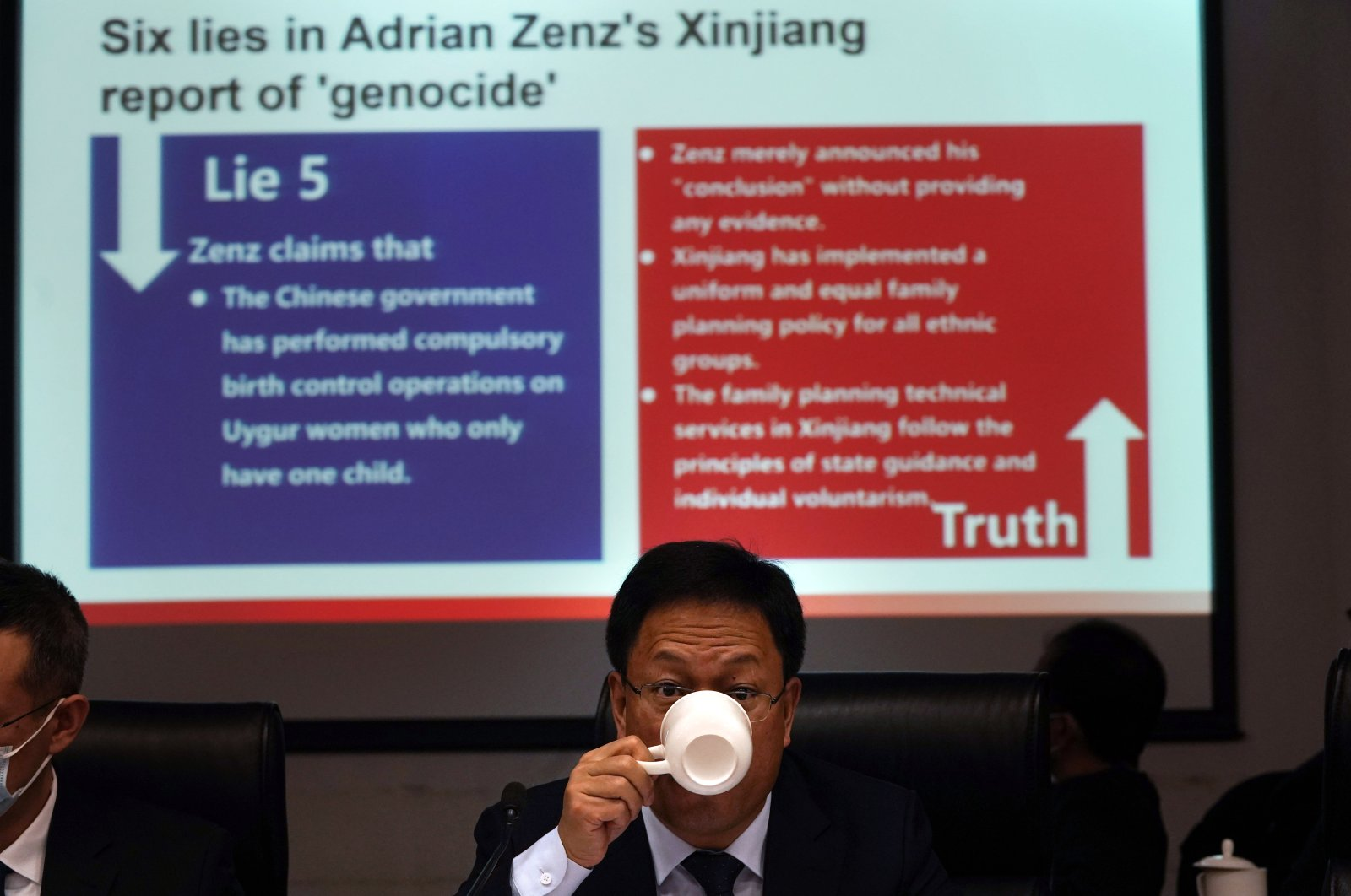 Xu Guixiang, a deputy spokesperson for the Xinjiang regional government, drinks from a cup near a slide refuting claims of genocide during a press conference in Beijing, China, Jan. 11, 2021. (AP Photo)