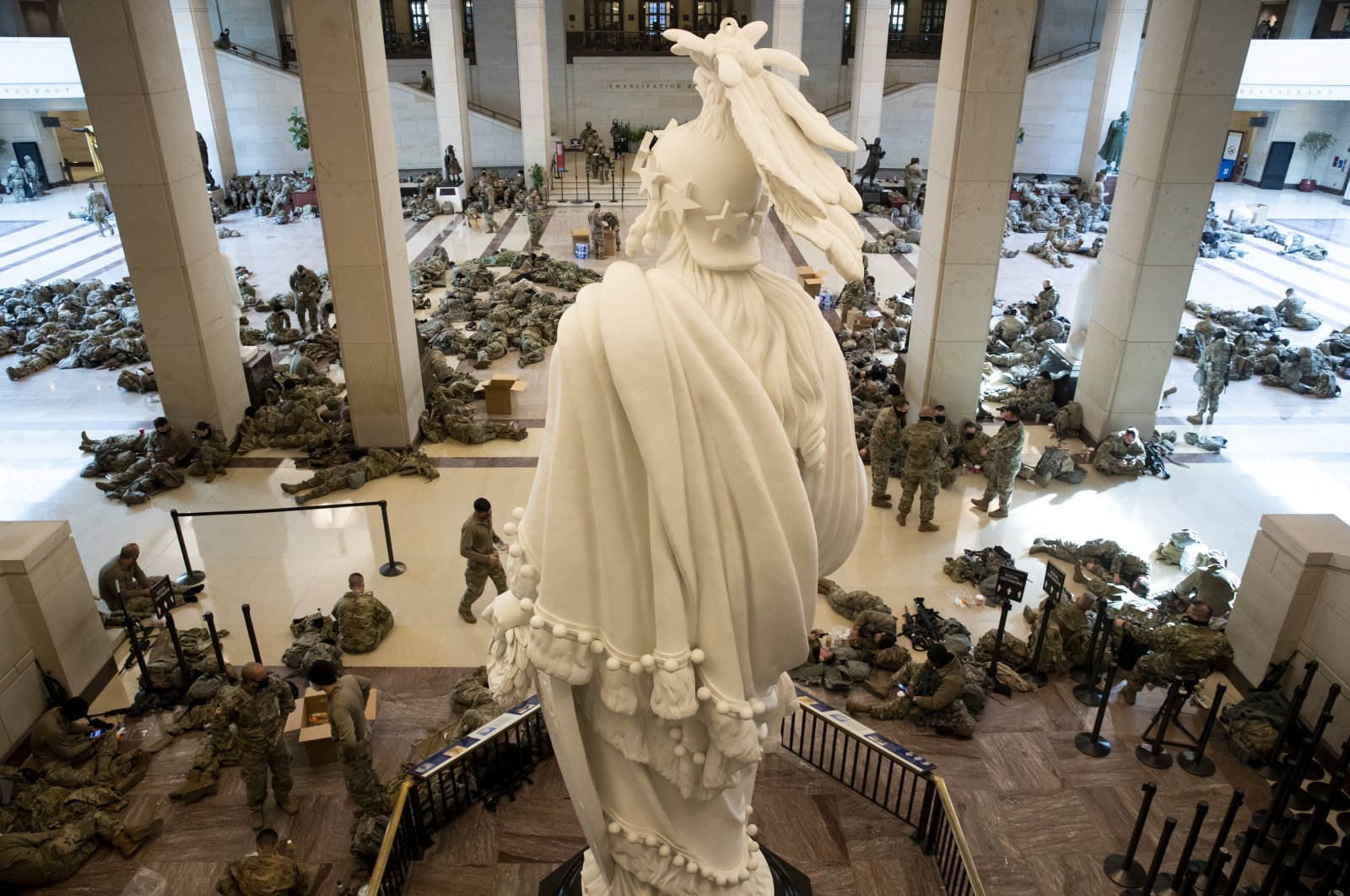 Hundreds of US National Guard troops rest in the Capitol Visitors Center, with the Statue of Freedom seen at center, on Capitol Hill in Washington, DC, USA, 13 January 2021. (EPA Photo)