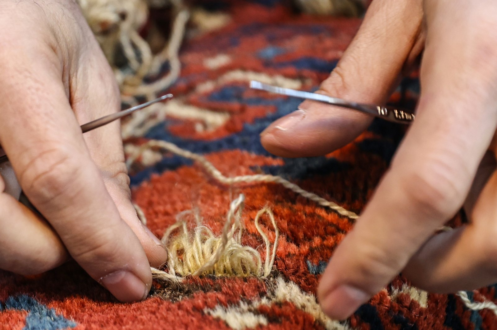 A close-up of Ramazan Yumuşak's hands while repairing a carpet at his workshop in the Babıali Carpetmakers Bazaar, Istanbul, Turkey, Jan. 10, 2021. (AA Photo)