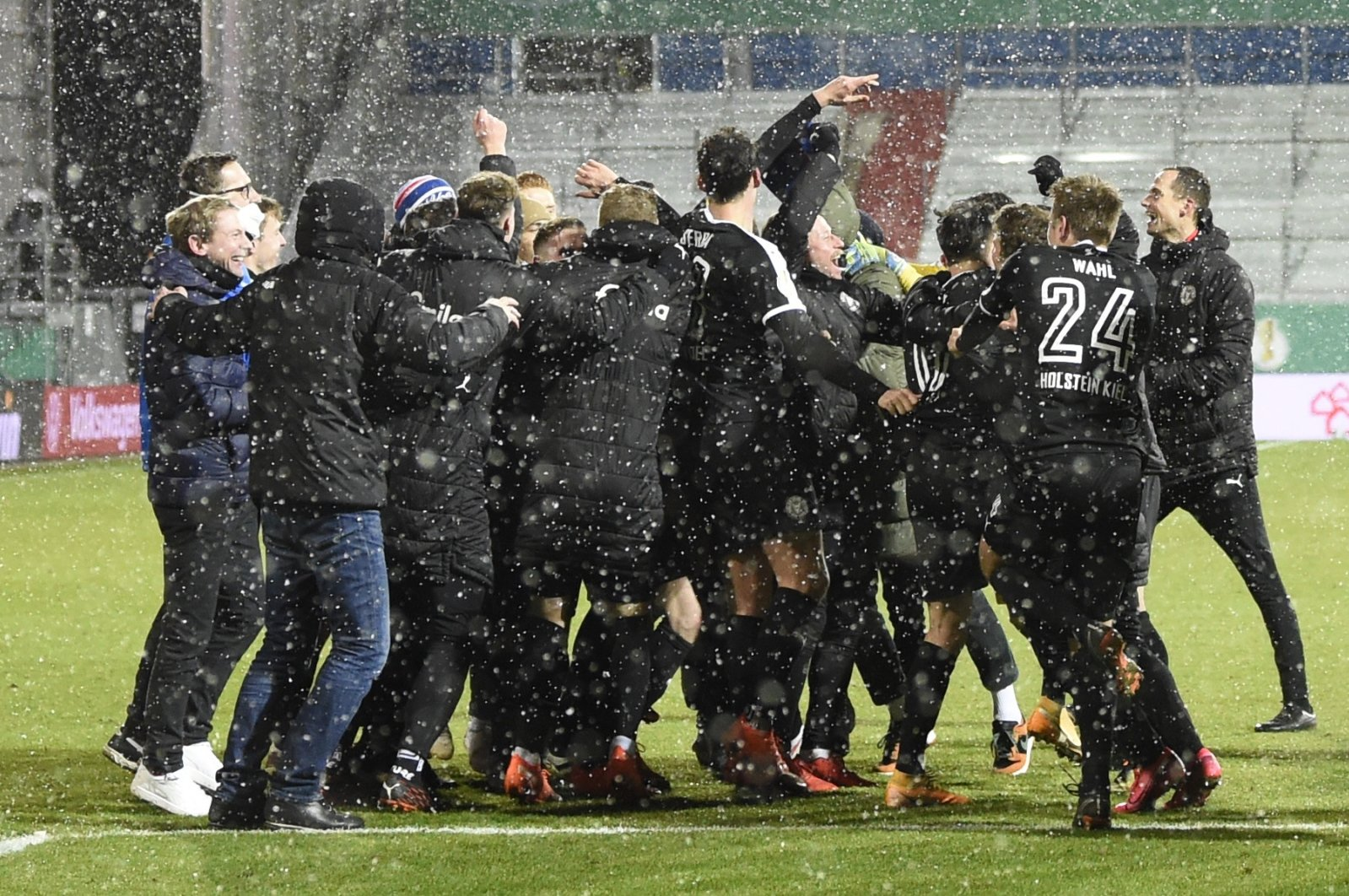 Kiel's players celebrate after beating Bayern Munich during the DFB Cup 2nd round match between Holstein Kiel and Bayern Munich at the Holstein Stadium in Kiel, Germany, Wednesday Jan. 13, 2021. (Reuters Photo)