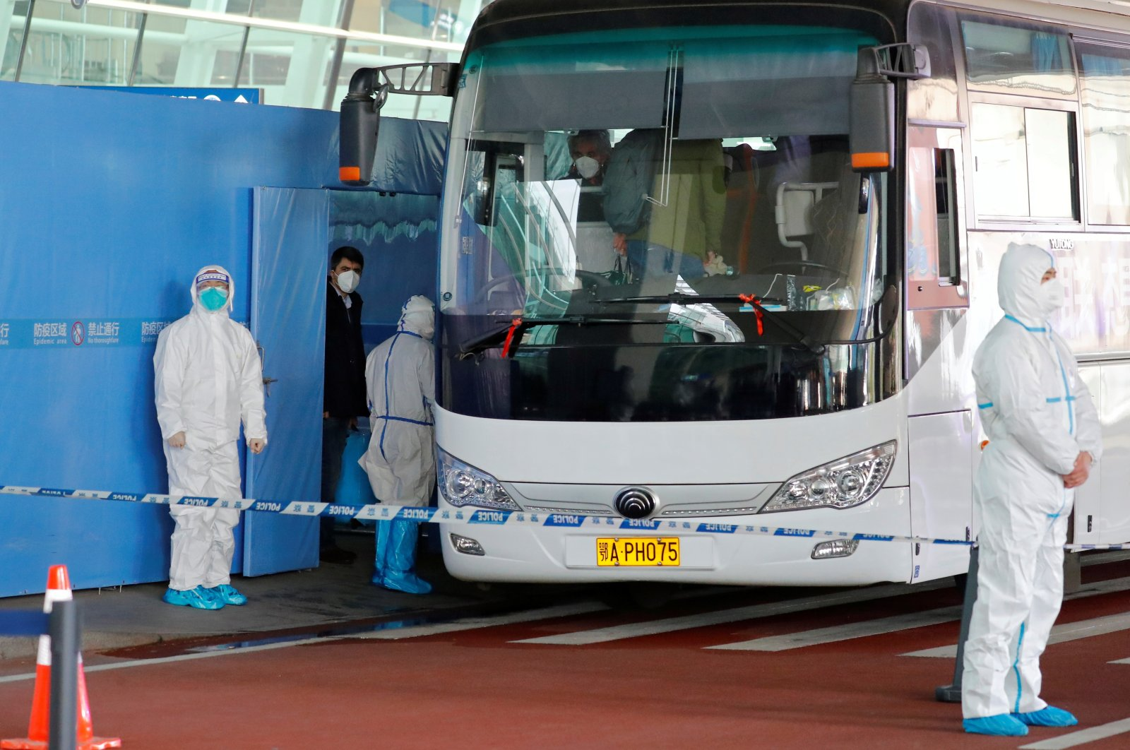 Members of the World Health Organization (WHO) team tasked with investigating the origins of the COVID-19 pandemic board a bus before leaving Wuhan Tianhe International Airport in Wuhan, Hubei province, China, Jan. 14, 2021. (Reuters Photo)