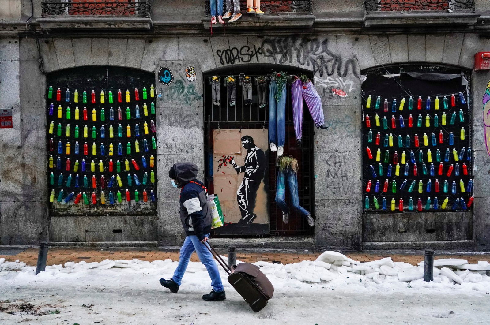 A man walks with a suitcase on a snow-covered street in the center of Madrid, Spain, Jan. 13, 2021. (Reuters Photo)