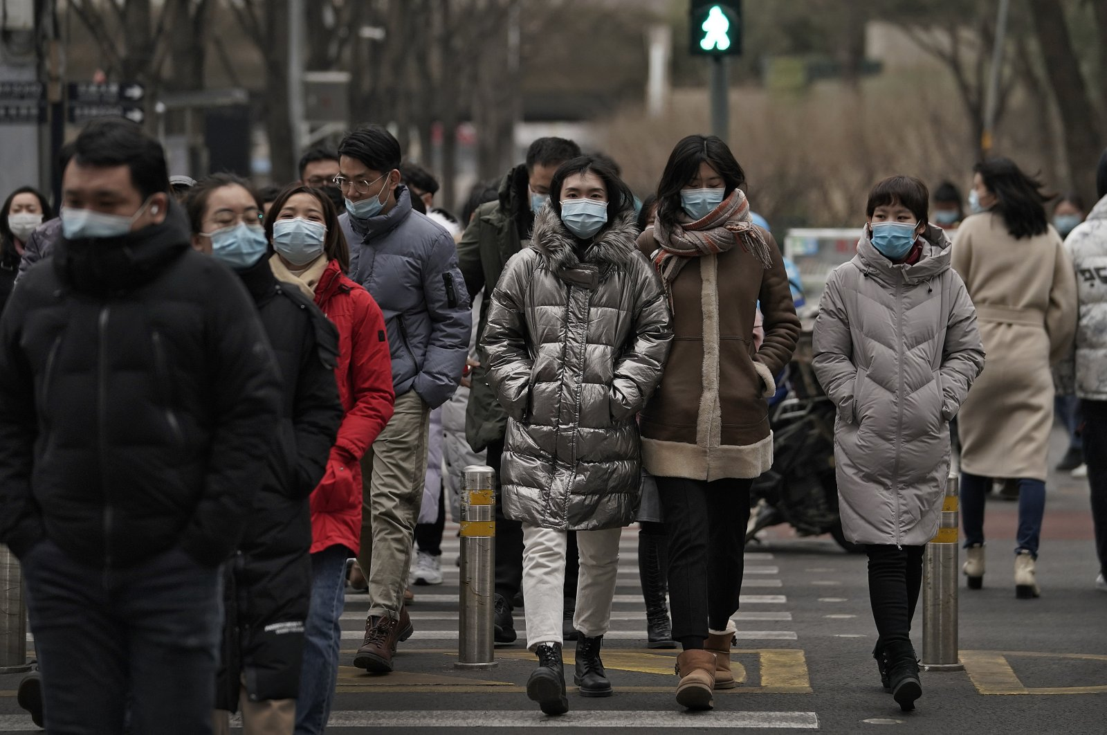 People wearing masks to help curb the spread of the coronavirus walk across a street during a lunch break, Beijing, China, Jan. 14, 2021. (AP Photo)