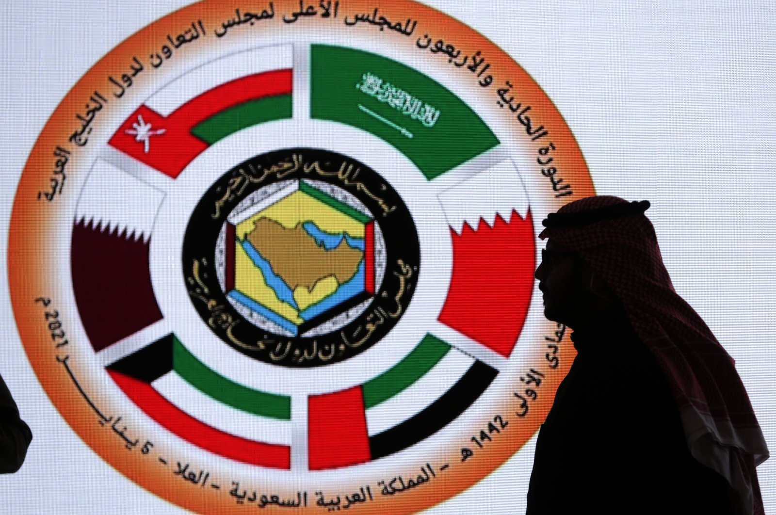 A Saudi television anchor stands in front of the logo of the 41st Gulf Cooperation Council (GCC) at the media center in Al Ula, Saudi Arabia, Jan. 5, 2021. (AP Photo)