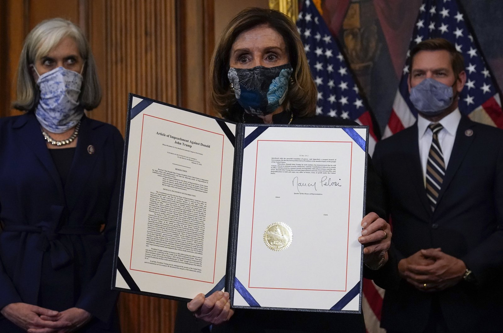 House Speaker Nancy Pelosi displays the signed article of impeachment against President Donald Trump during an engrossment ceremony before transmission to the Senate for a trial on Capitol Hill, in Washington, D.C., U.S., Jan. 13, 2021. (AP Photo/Alex Brandon)