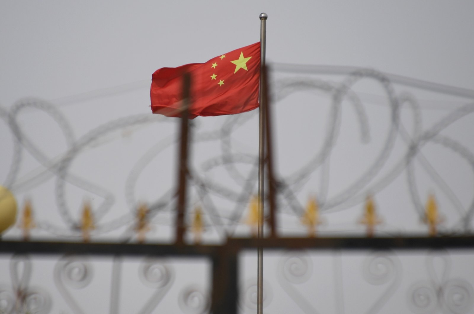 The Chinese flag flies behind razor wire at a housing compound in Yangisar, south of Kashgar, in China's western Xinjiang region, June 4, 2019. (Photo provided by Badung police via AFP)