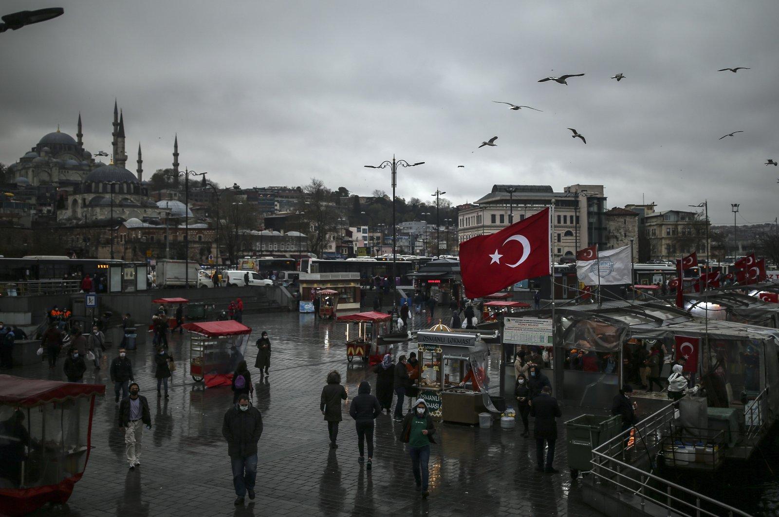 People walk around the Eminönü neighborhood by the Golden Horn in Istanbul, Turkey, Dec. 15, 2020. (AP Photo)