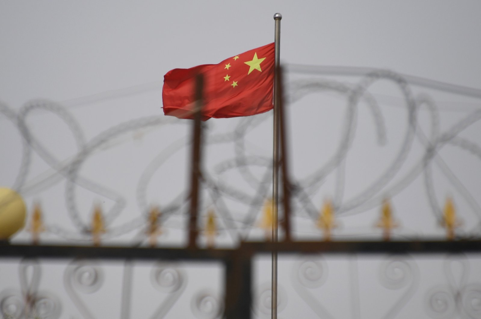 This file photo taken on June 4, 2019, shows the Chinese flag behind razor wire at a housing compound in Yangisar, south of Kashgar, in China's western Xinjiang region. (AFP Photo)