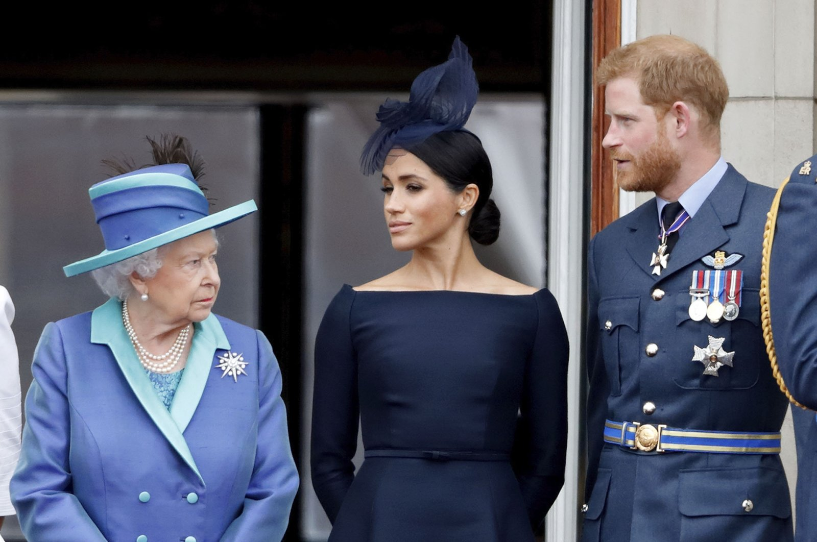 Queen Elizabeth II, Meghan, Duchess of Sussex and Prince Harry, Duke of Sussex watch a flypast to mark the centenary of the Royal Air Force from the balcony of Buckingham Palace, London, July 10, 2018. (Getty Images)