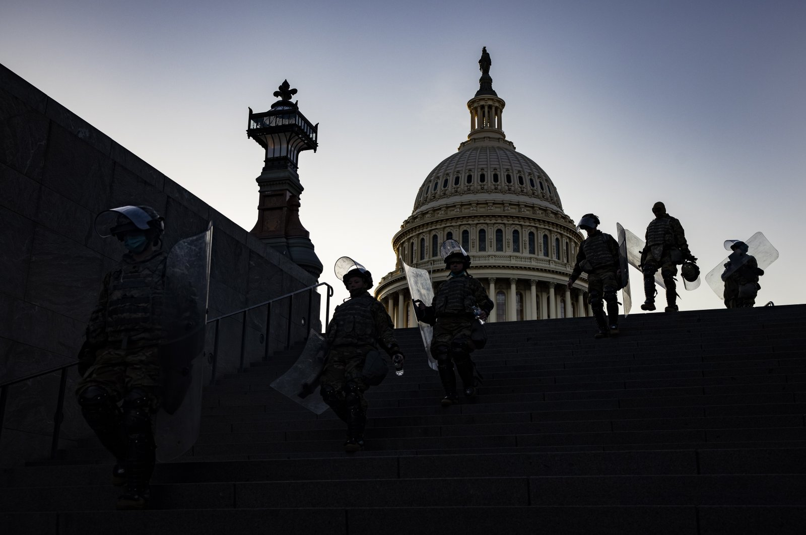 National Guard soldiers with riot shields head to the Capitol Visitors Center after being deployed to secure the grounds around the US Capitol building in Washington, DC, USA, 13 January 2021. (EPA Photo)