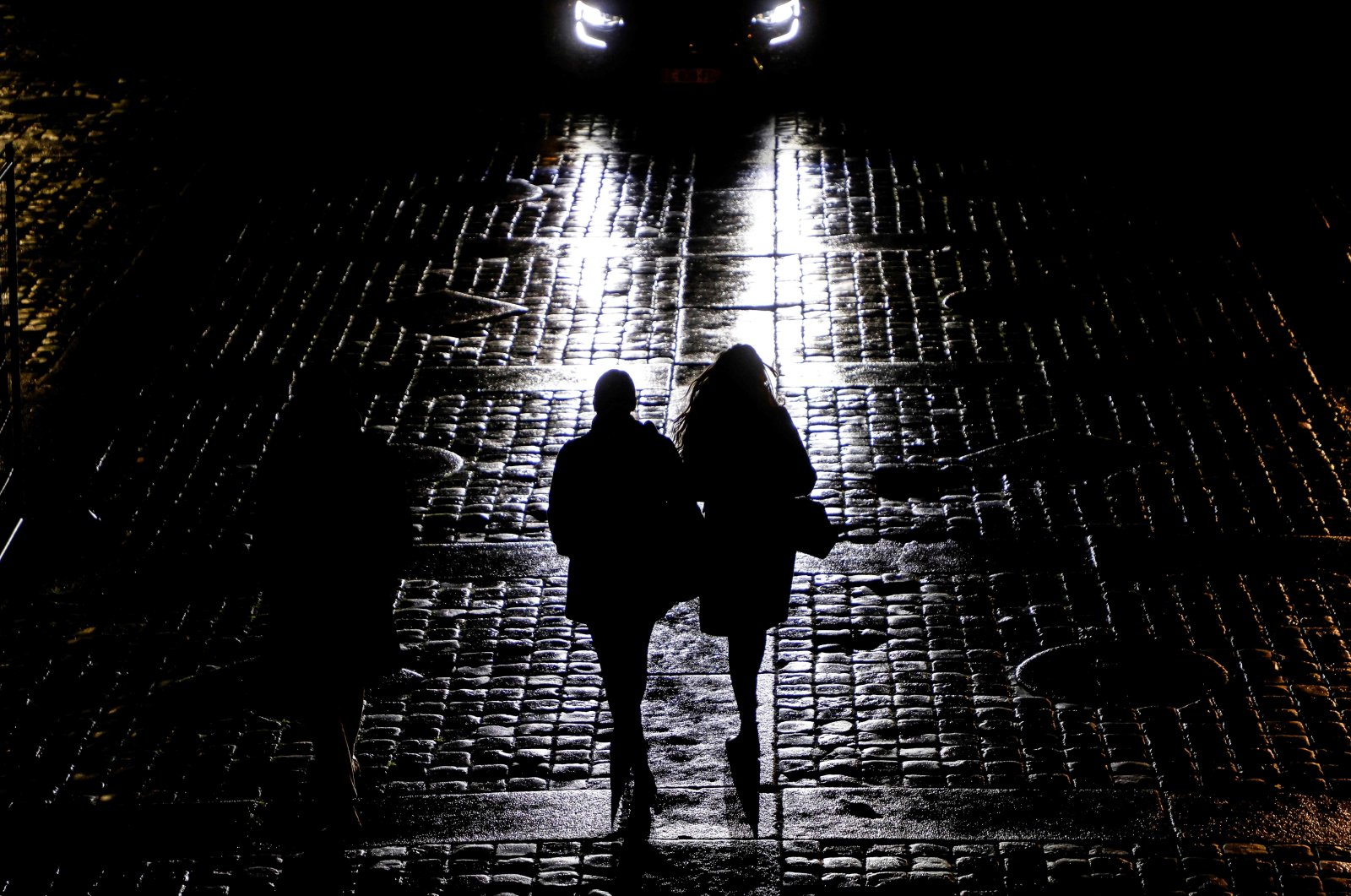 """People are seen in silhouette from car headlights as they leave the """"Palais de Justice"""" courthouse in Paris, on January 14, 2021. (AFP Photo)"""