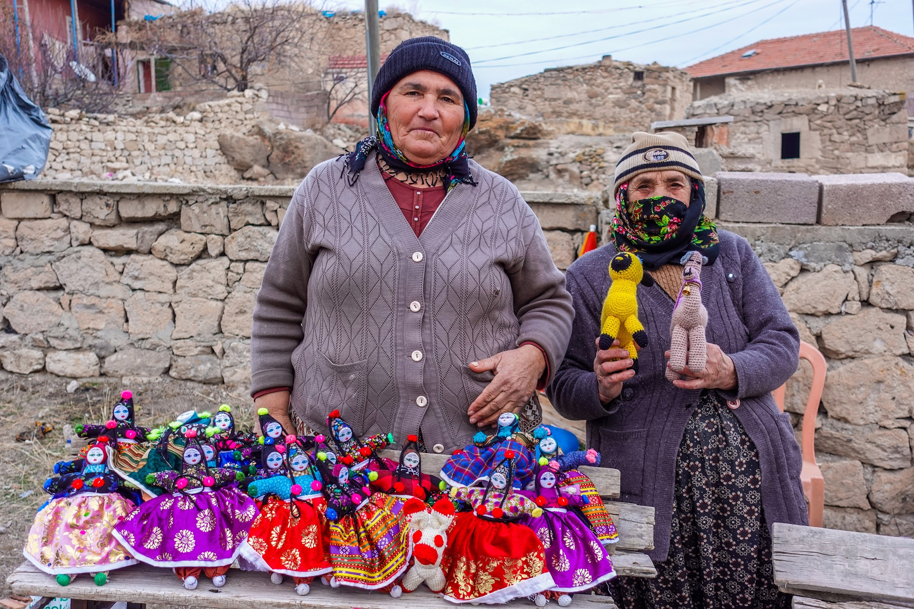 Hayriye Teyze (R) and Ayşe Teyze pose with their handmade dolls. (Photo by Argun Konuk)
