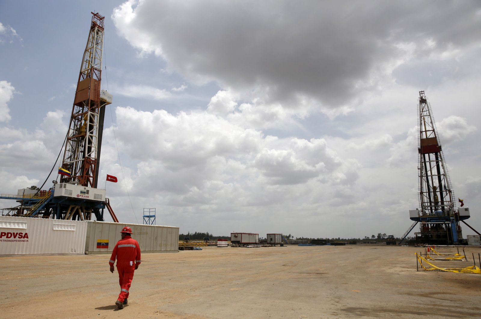 An oilfield worker walks next to drilling rigs at an oil well operated by Venezuela's state oil company PDVSA, in the oil-rich Orinoco belt, Venezeula, April 16, 2015. (Reuters Photo)