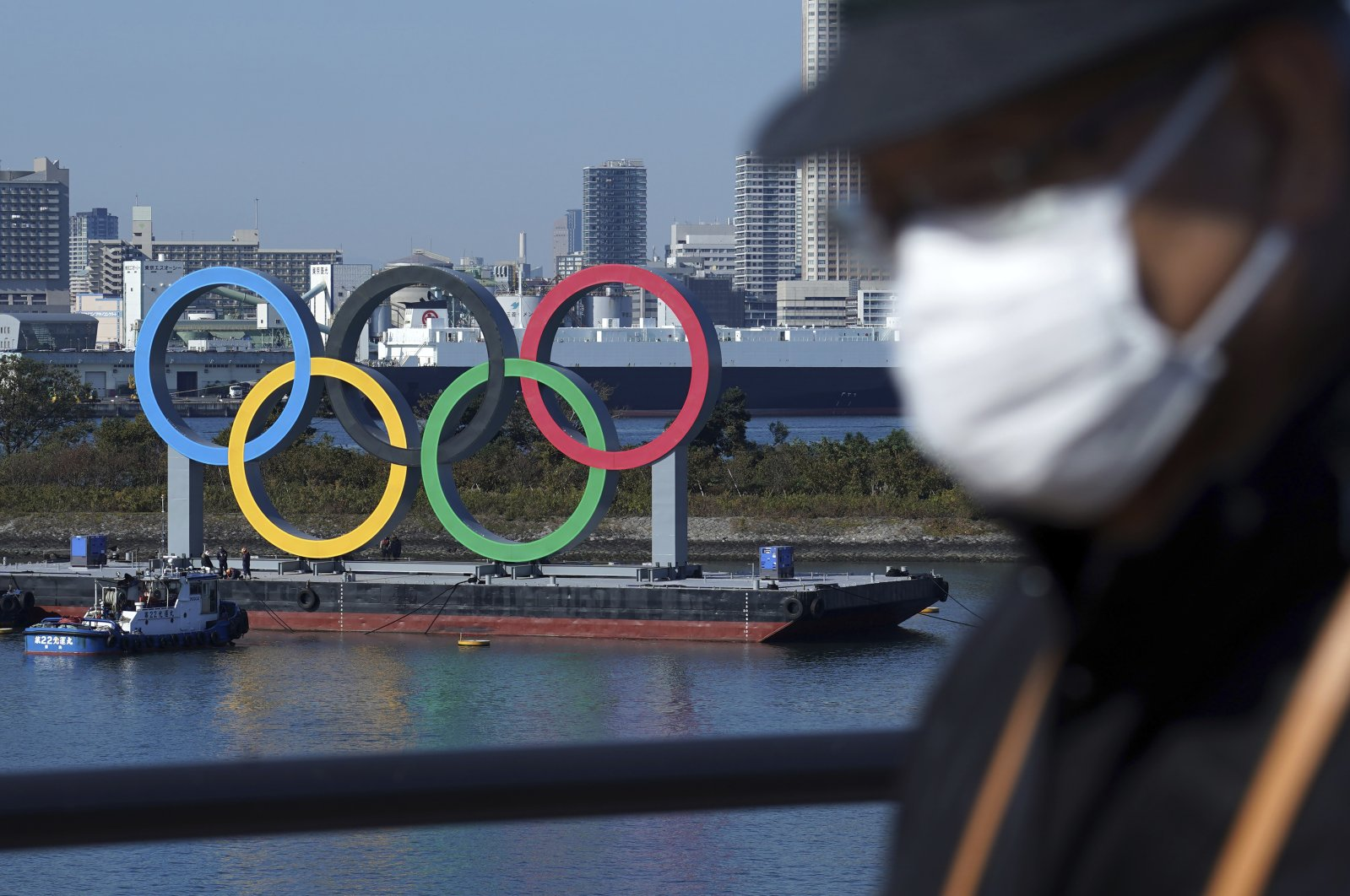 A man wearing a face mask walks with the Olympic rings in the background, in Tokyo, Japan, Dec. 1, 2020. (AP Photo)