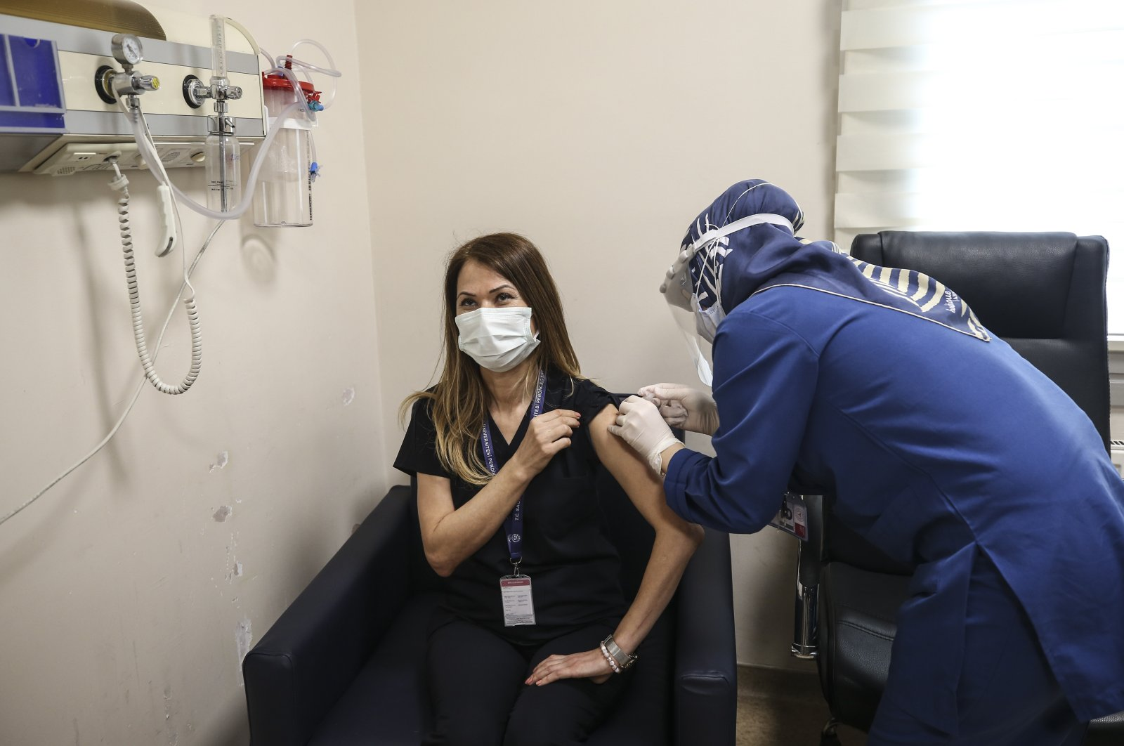 A nurse administers a dose of the vaccine to health care worker Fatma Çırpı at a hospital in Istanbul, Turkey, Jan. 14, 2021. (AP Photo)
