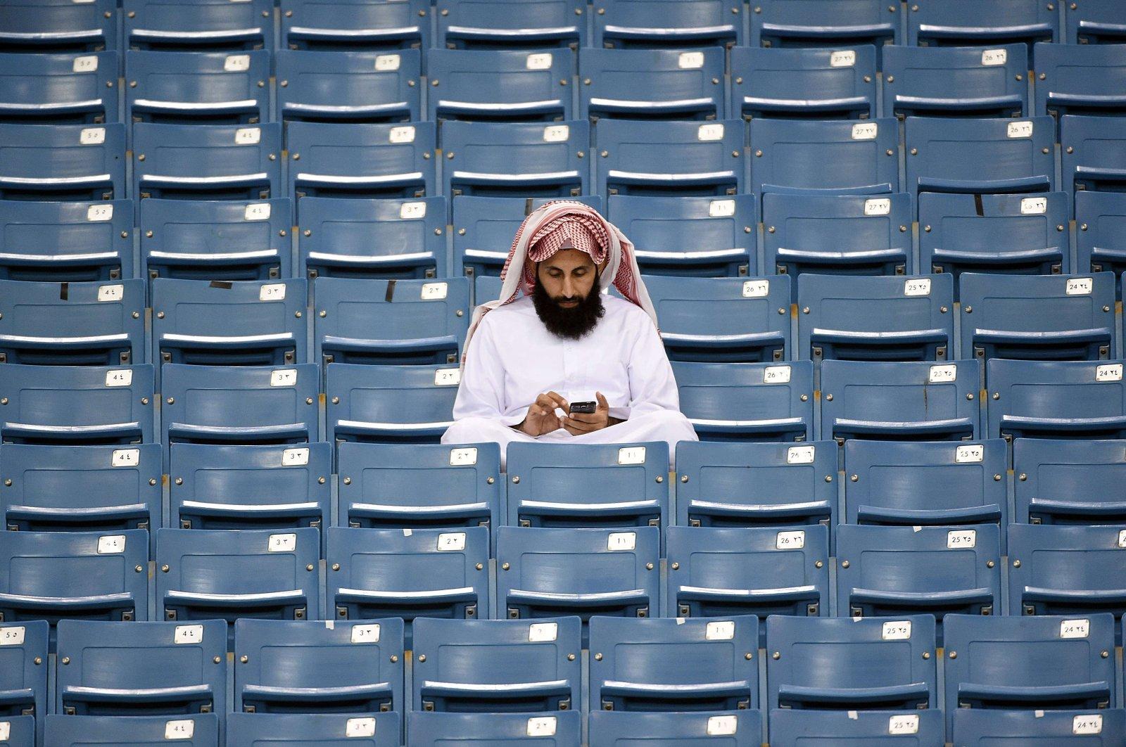 A Saudi Arabian fan checks his mobile phone before the final of the 22nd Gulf Cup of Nations football match against Saudi Arabia at the King Fahad stadium in Riyadh, Saudi Arabia, Nov. 26, 2014. (AFP Photo)