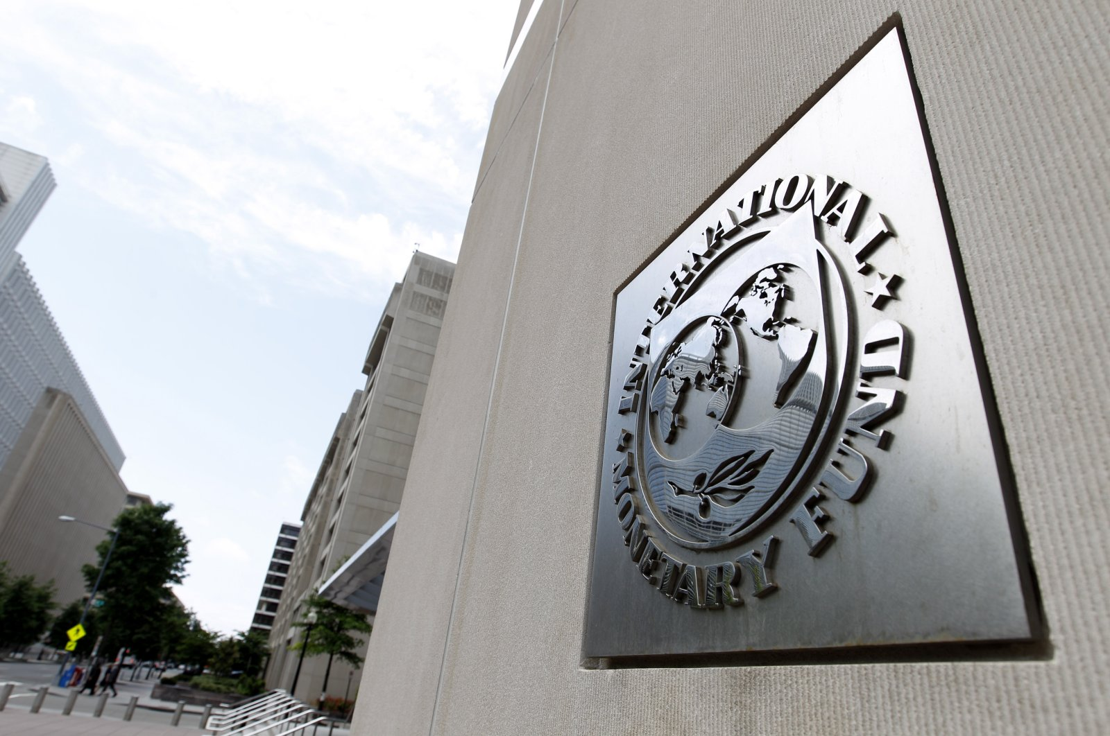 Pedestrians pass by the International Monetary Fund headquarters building in Washington, D.C., May 15, 2011. (AP Photo)