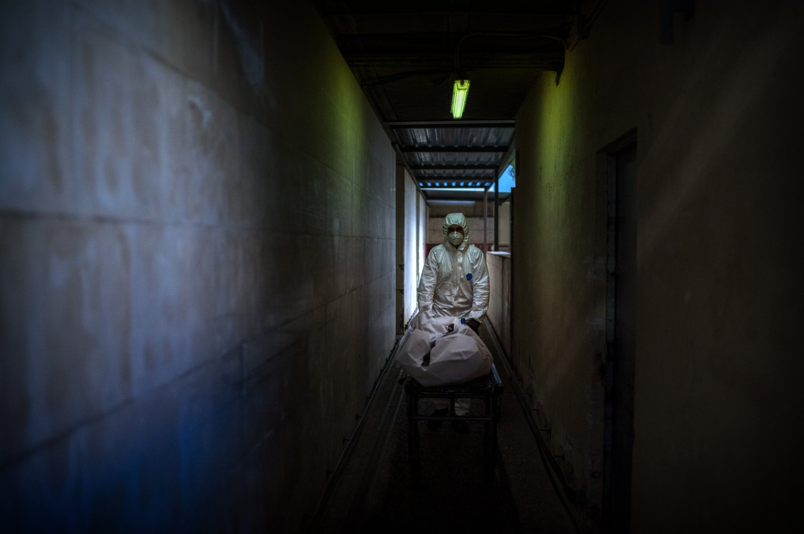 A mortuary worker transports the body of a COVID-19 victim on a stretcher at the morgue of a hospital in Barcelona, Spain, Nov. 5, 2020. (AP Photo)