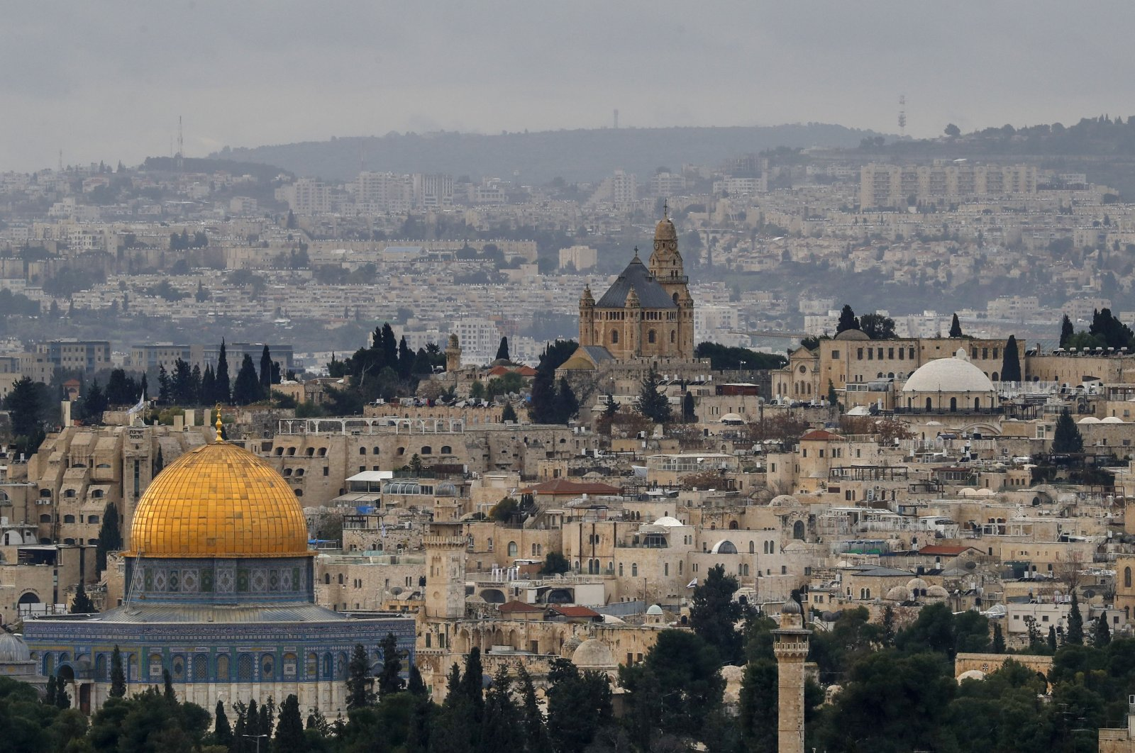 The Dome of the Rock (L), in the Al-Aqsa mosques compound and the Abbey of the Dormition (C) on Mount Zion, a Benedictine Basilica, built over the site where the Virgin Mary is said to have fallen asleep for the last time, in the Old City of Jerusalem, Jan. 15, 2021. (AFP Photo)
