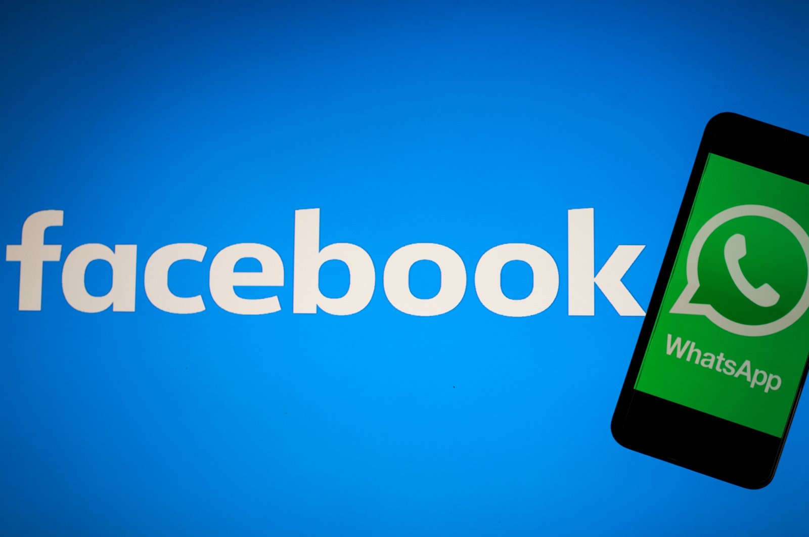 An illustration of the Facebook logo as the backdrop for the social network's WhatsApp logo on a smartphone. (AA Photo)