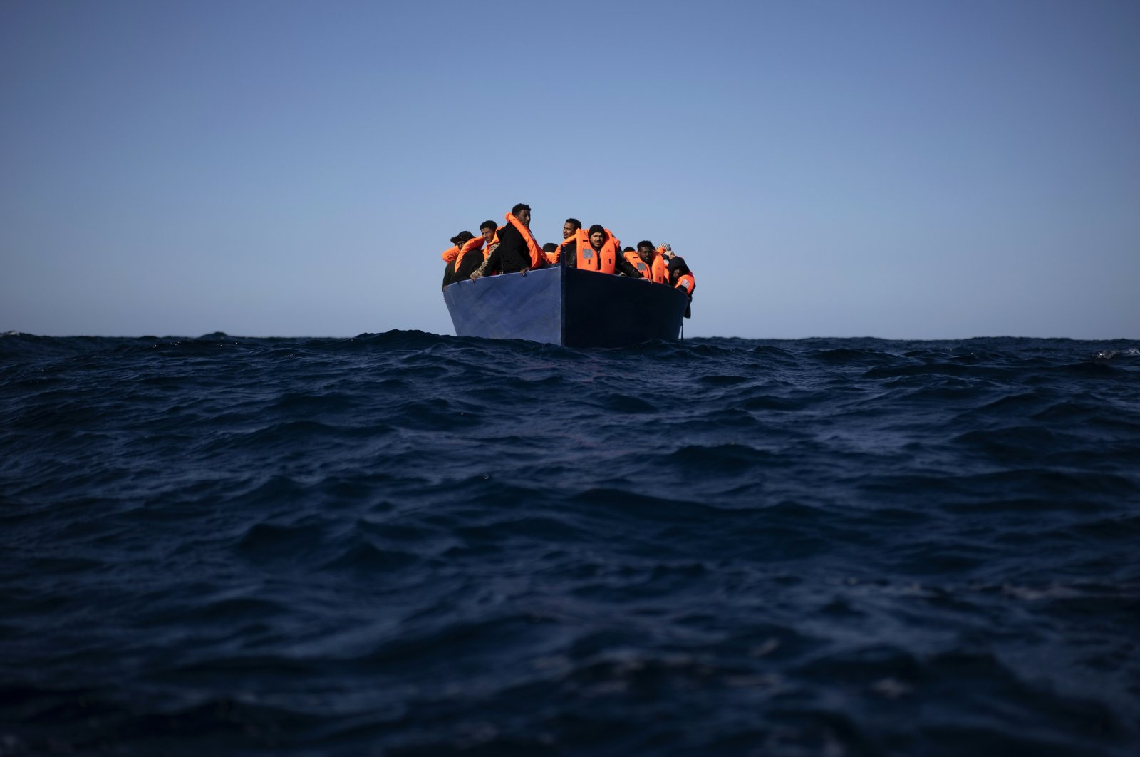 Migrants from Eritrea, Egypt, Syria and Sudan, wait to be assisted by aid workers of the Spanish NGO Open Arms, after fleeing Libya on board a precarious wooden boat in the Mediterranean sea, about 177 kilometers (110 miles) north of Libya, on Saturday, Jan. 2, 2021. (AP Photo)