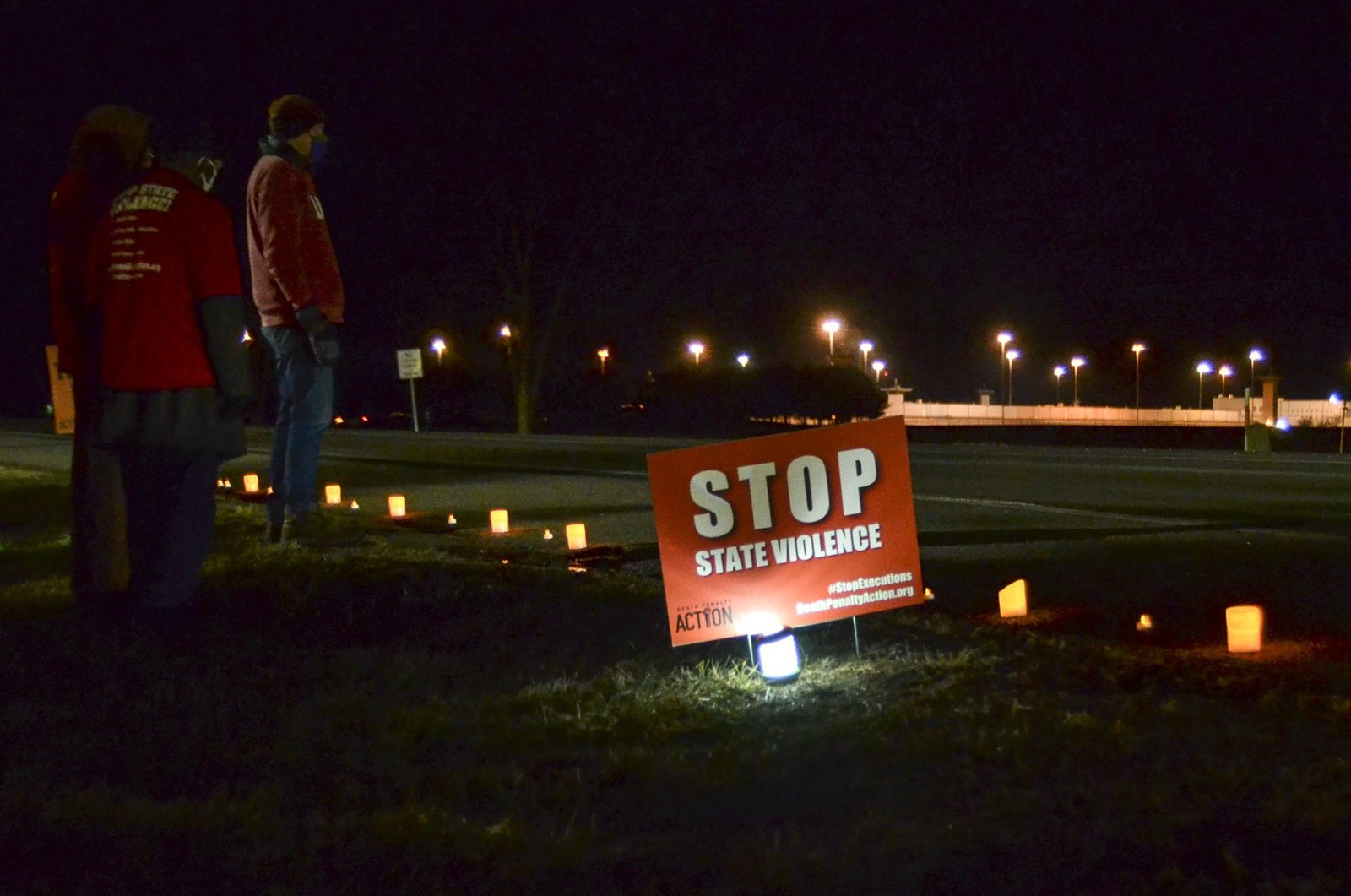 Protesters stand across Prairieton Road from the Federal Death Chamber in Terre Haute, Indiana, Jan. 15, 2021. (The Tribune-Star via AP)