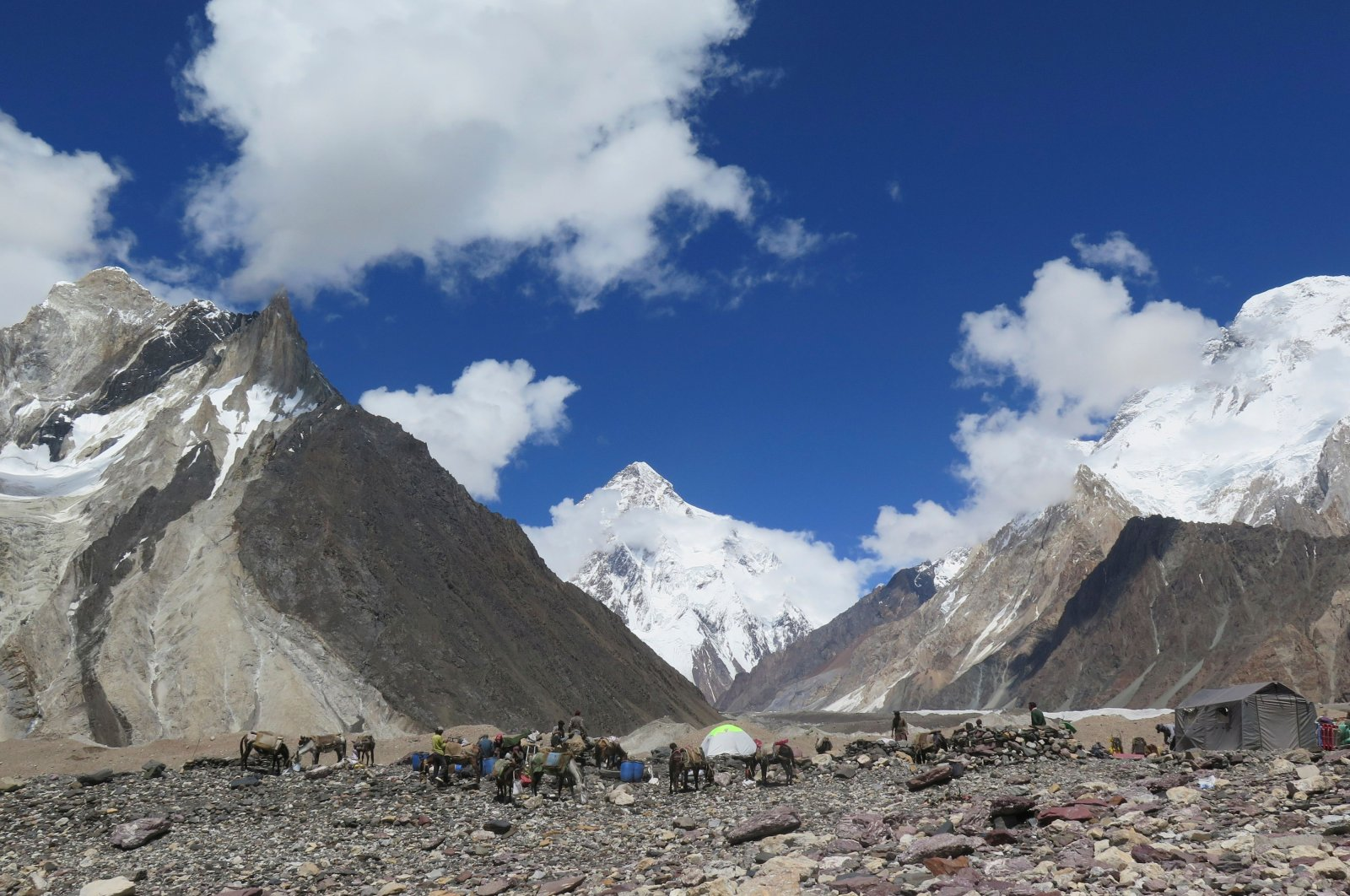 Porters set up tents at the Concordia camping site in front of the K2 summit (C) in the Karakoram range of the Gilgit region, northern Pakistan, Aug. 14, 2019. (AFP Photo)