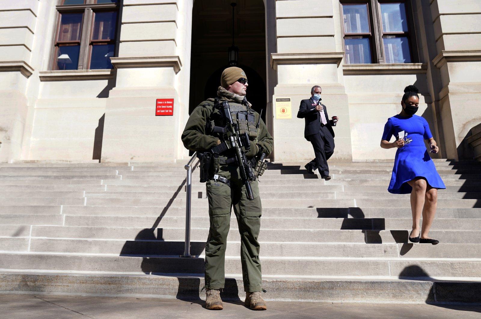 A Georgia State Patrol SWAT team member stands guard outside the Georgia State Capitol building in Atlanta, Georgia, U.S., Jan. 14, 2021.   (AP Photo)