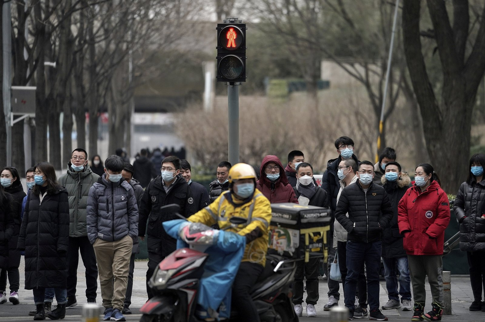 A food delivery worker and office workers wearing face masks to protect themselves from the coronavirus wait to cross a street in Beijing, China, Jan. 14, 2021. (AP Photo)