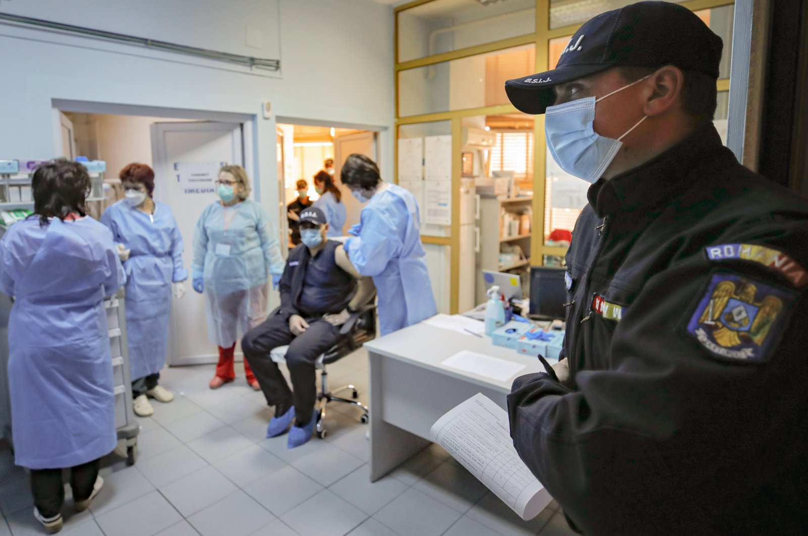 A Romanian gendarme waits to get a COVID-19 vaccine at a hospital in Bucharest, Romania, Jan. 15, 2021. (AP Photo)