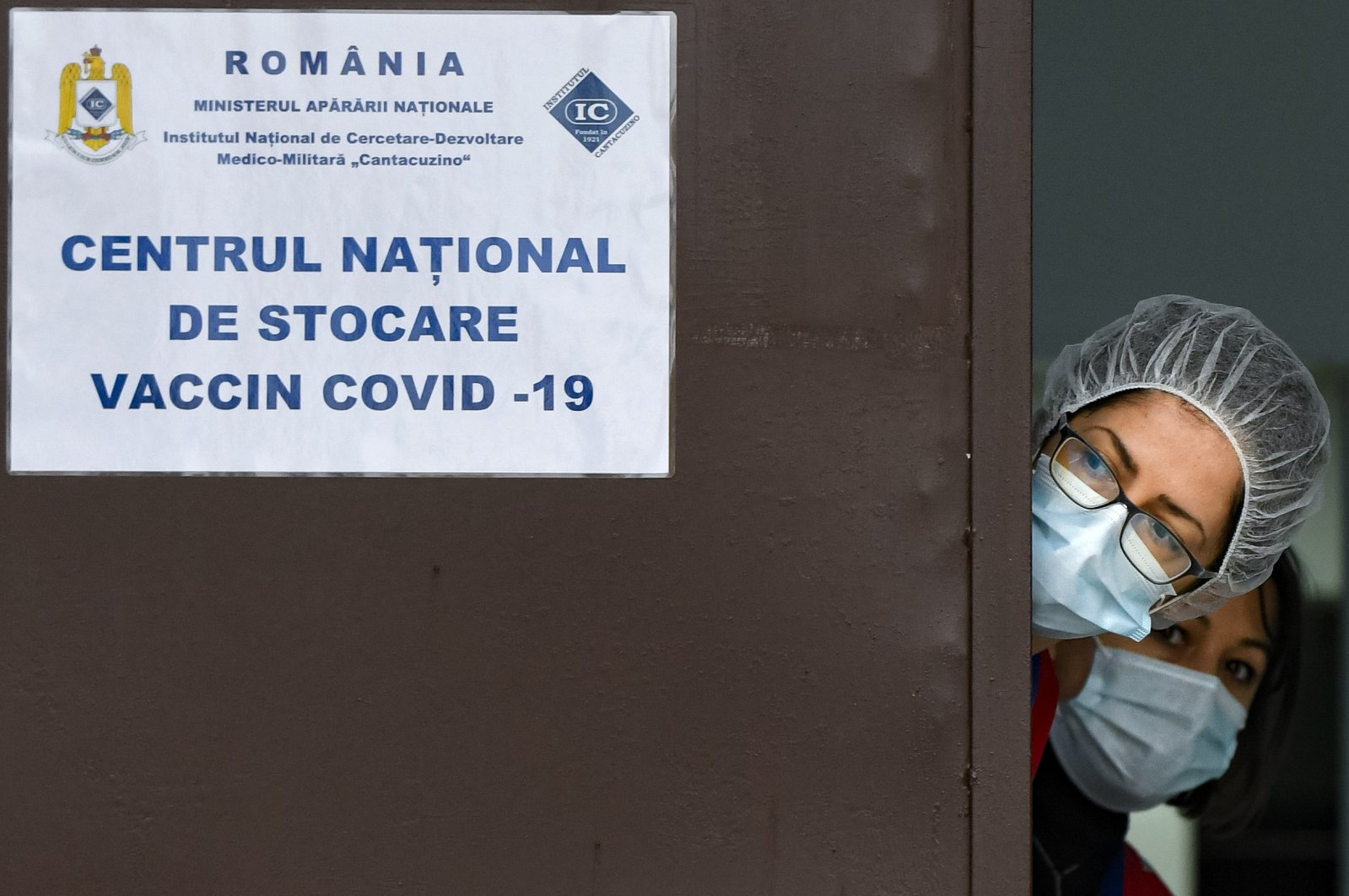 Medical staff peer from behind a door at the National Center for Storage of the COVID-19 Vaccine in Bucharest, Romania on Dec. 18, 2020. (AP Photo)