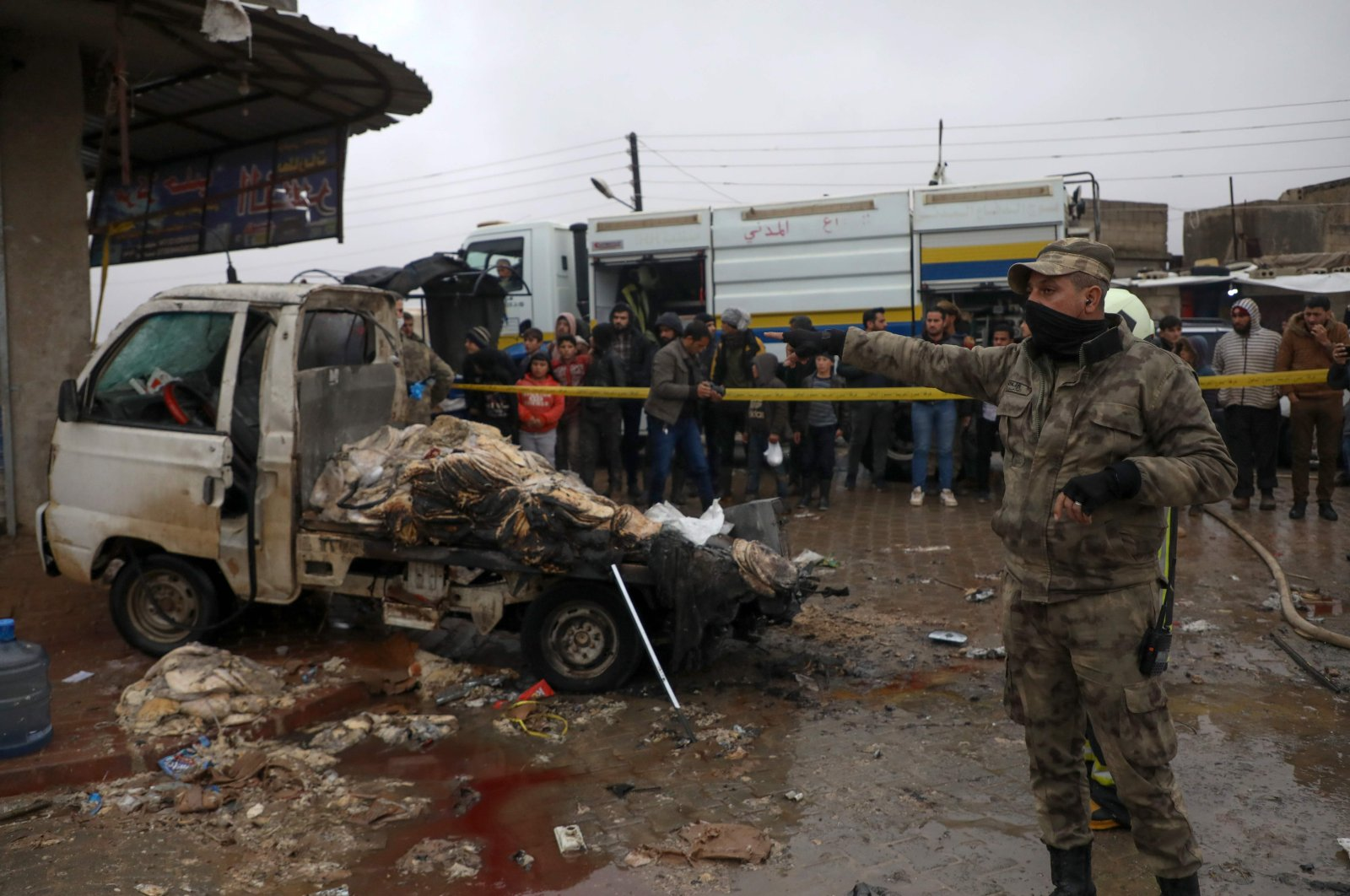 A Syrian opposition member gestures while standing in a pool of blood and water next to a damaged bread-delivery truck that exploded, killing at least one person and injuring at least six others, at the entrance of a market in the town of Saju near Azaz in the opposition-controlled northern countryside of Syria's Aleppo province, on Jan. 17, 2021. (AFP Photo)