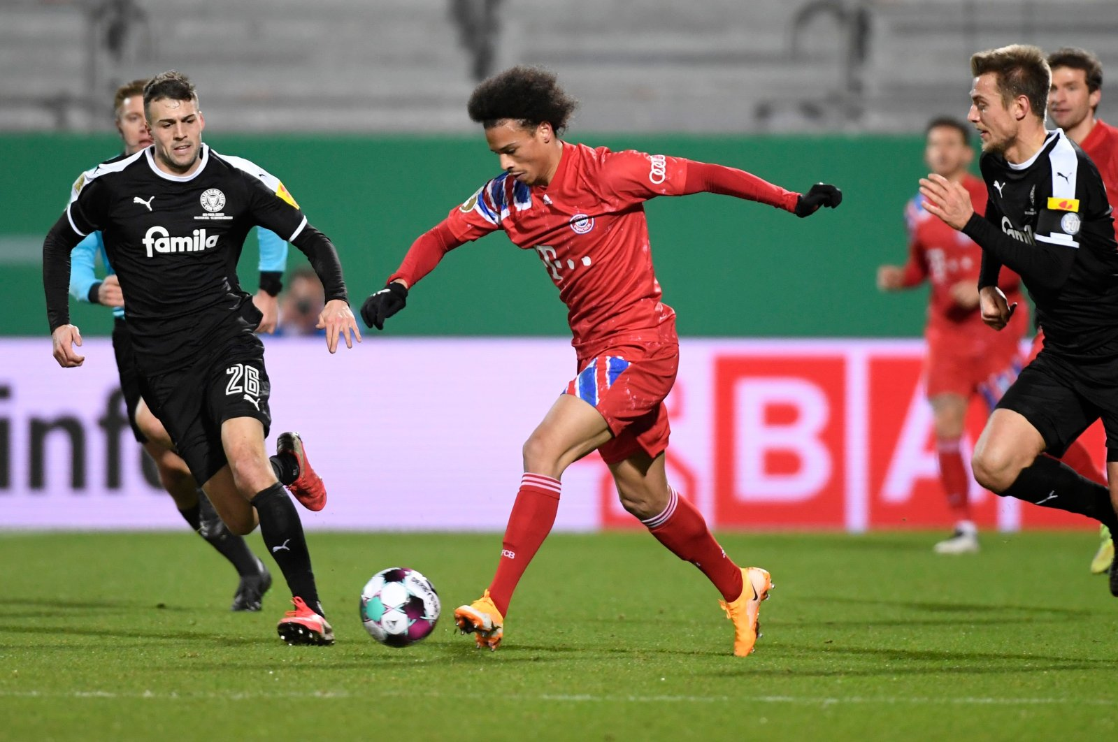 Bayern Munich's Leroy Sane (C) vies for the ball with Holstein Kiel's Jonas Meffert (L) during a match in Kiel, Germany, Jan. 13, 2021. (AFP PHOTO)