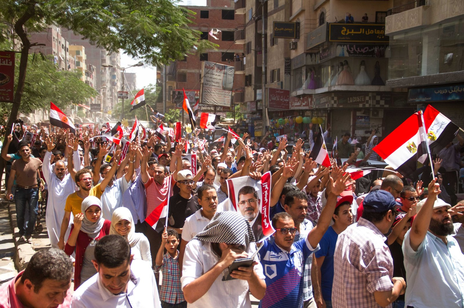 Members of the Muslim Brotherhood hold up pictures of their ousted President Mohammed Morsi during protests, Egypt, Aug. 14, 2015. (AP Photo)