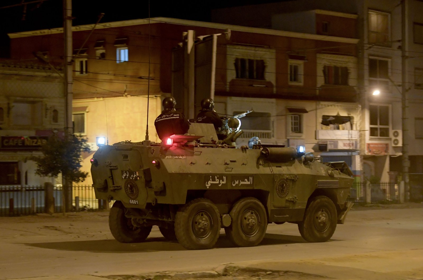 Members of the Tunisian National Guard sit atop their armored vehicle as they deploy on a street amid clashes with demonstrators following a protest in the Ettadhamen neighborhood in the capital Tunis, on Jan. 17, 2021. (AFP Photo)