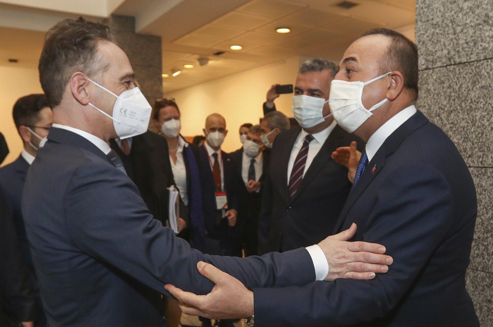 Turkey's Foreign Minister Mevlüt Çavuşoğlu (R) greets Germany's Foreign Minister Heiko Maas (L) prior to their meeting, in the capital Ankara, Turkey, Jan. 18, 2021. (Turkish Foreign Ministry via AP Photo)