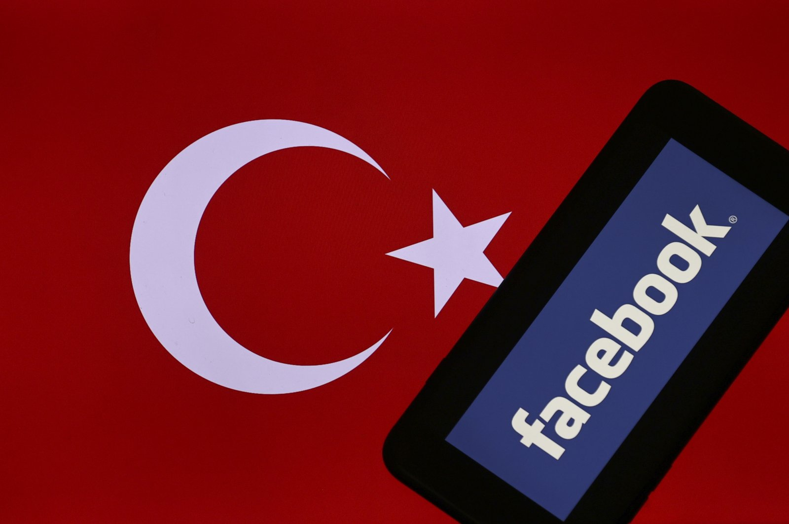 The Facebook logo is seen on a mobile phone screen with the Turkish flag in the background in this illustration photo, in the capital Ankara, Turkey, Jan. 18, 2021. (AA Photo)