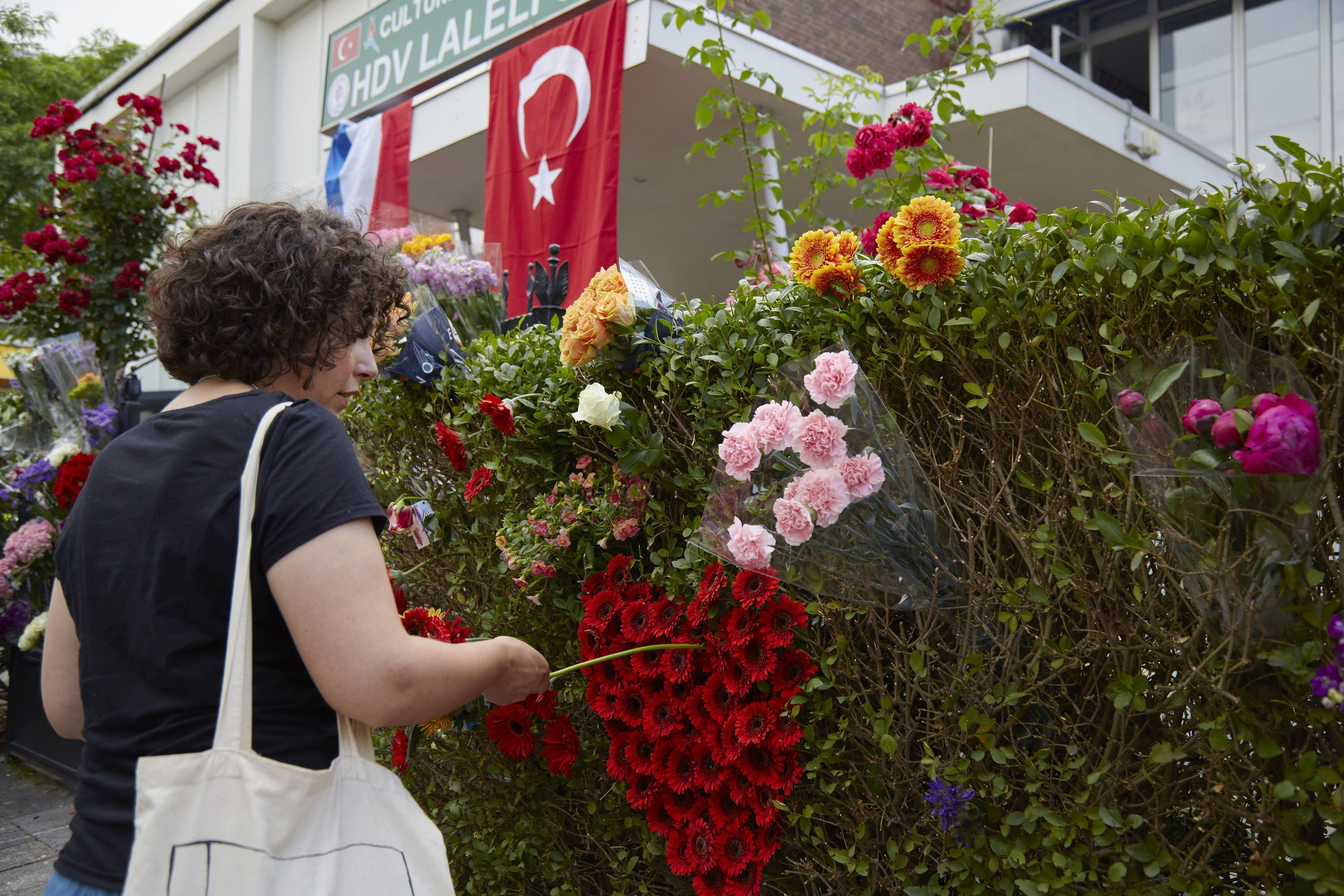 A woman makes a heart with flowers outside the Laleli Mosque as anti-Islam group Pegida plans to roast pigs on a barbecue outside the mosque during the month of Ramadan has failed, Rotterdam, Netherlands, June 7, 2018. (Getty Images)