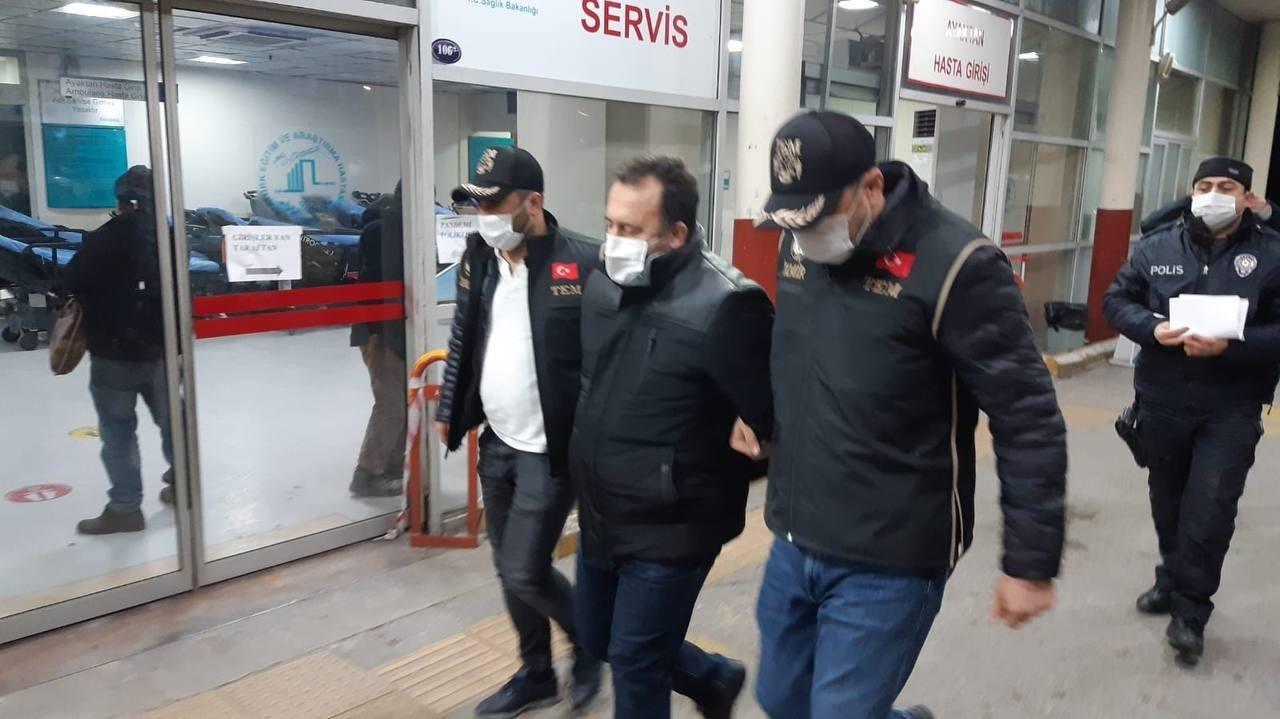Police escort a suspect to get medical checks after his arrest, in Izmir, western Turkey, Jan. 19, 2021. (AA PHOTO)