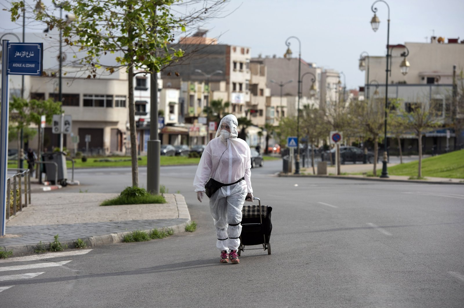 A Moroccan woman wearing protective clothing, volunteers to buy the necessary supplies from the shops and distribute them to the needy in Rabat, Morocco, April 18, 2020. (EPA Photo)