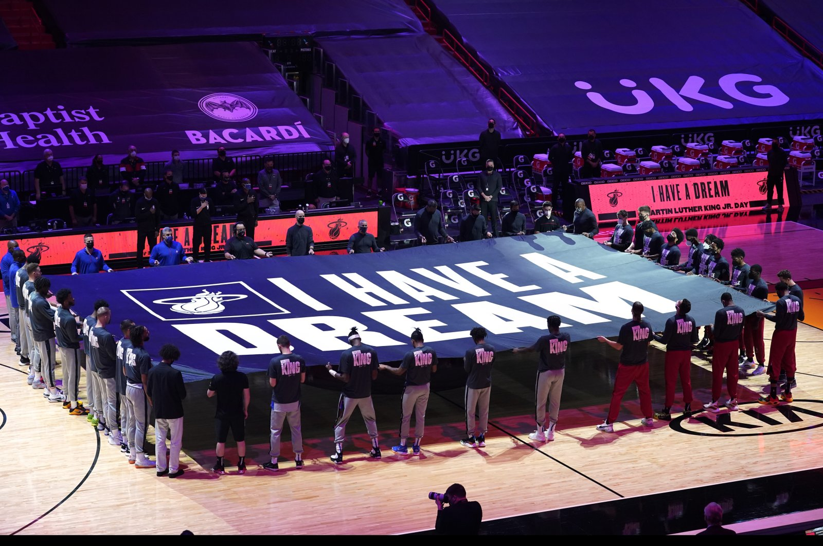 """Miami Heat and Detroit Pistons players hold a """"I Have a Dream"""" banner in honor of the Martin Luther King Jr., holiday before an NBA basketball game, in Miami, Florida, U.S., Jan. 18, 2021. (AP Photo/Marta Lavandier)"""