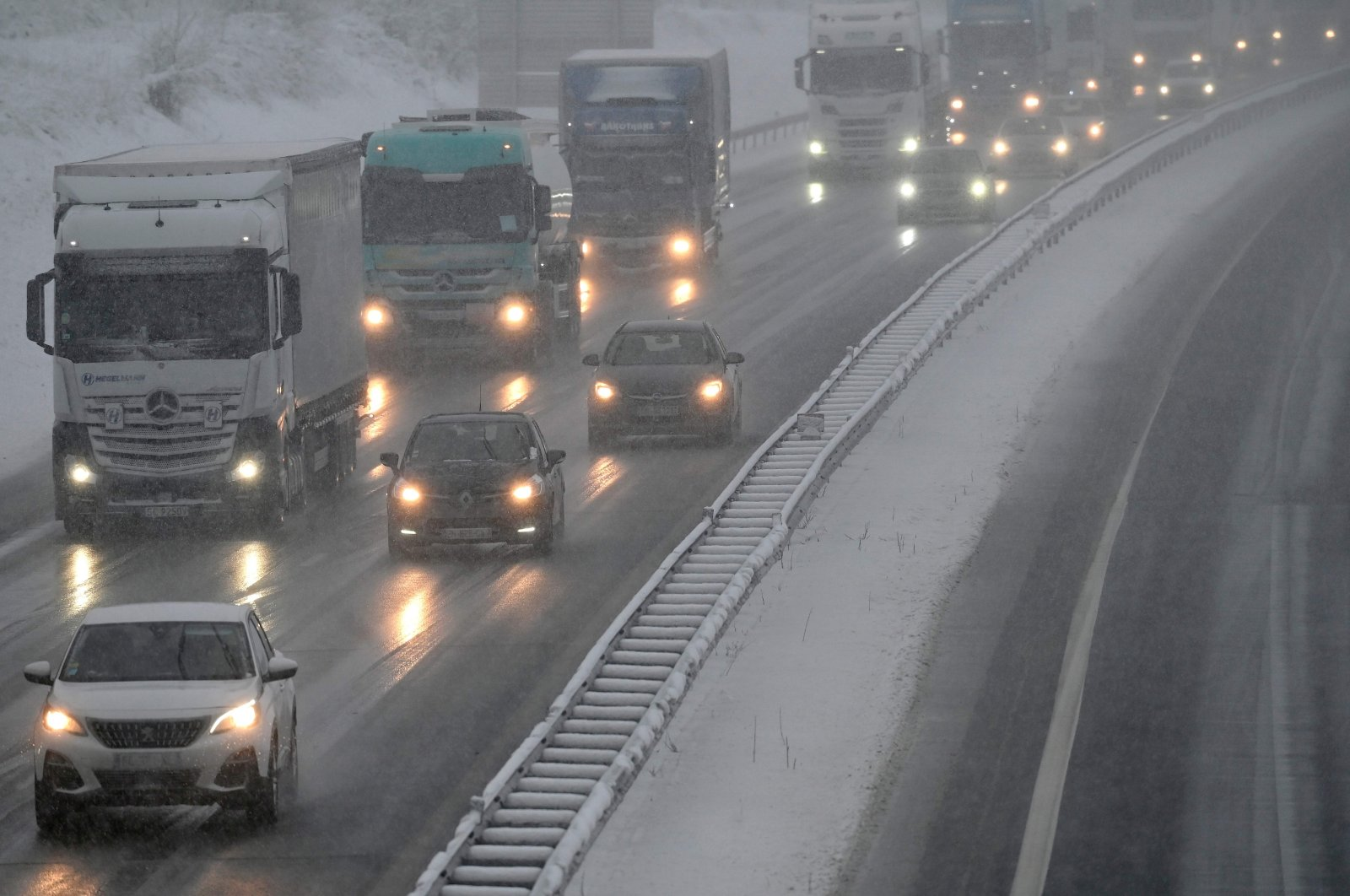 Cars and trucks on the A36 highway as the snow falls in Brunhaupt-le-Haut, France, on Jan. 14, 2021. (AFP Photo)