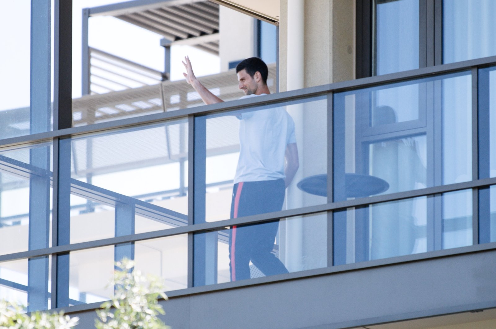 Tennis star Novak Djokovic waves from his balcony at accommodations where he is quarantining in advance of the Australian Open to be played in Melbourne, in North Adelaide, Australia, Jan. 19, 2021.  (AAP Image/Morgan Sette via Reuters)