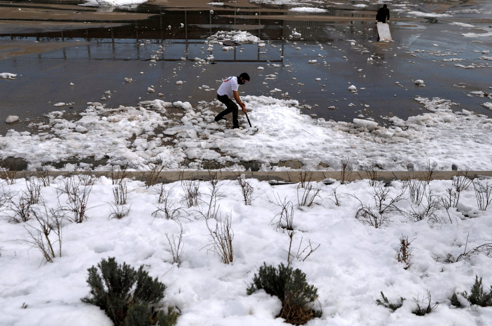 Members of a skating club clear ice and snow from the public area where they train after heavy snowfall in Madrid, Spain on Jan. 15, 2021. (Reuters Photo)
