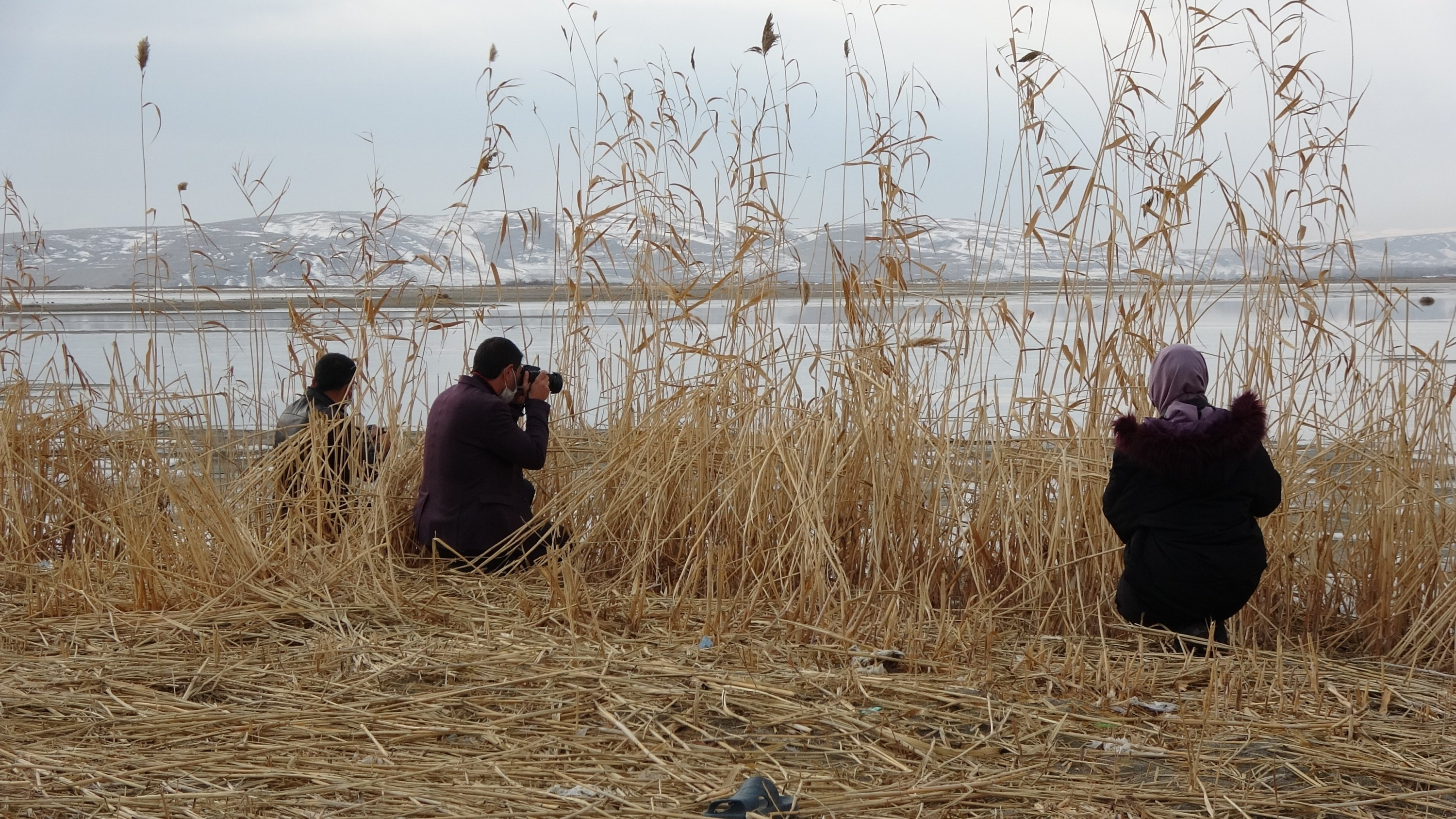 Nature photographers Meryem Bilgin (R) and Cafer Şahan (M) take pictures, along with another fellow enthusiast, at Lake Van, eastern Turkey, Jan. 19, 2021. (AA Photo)