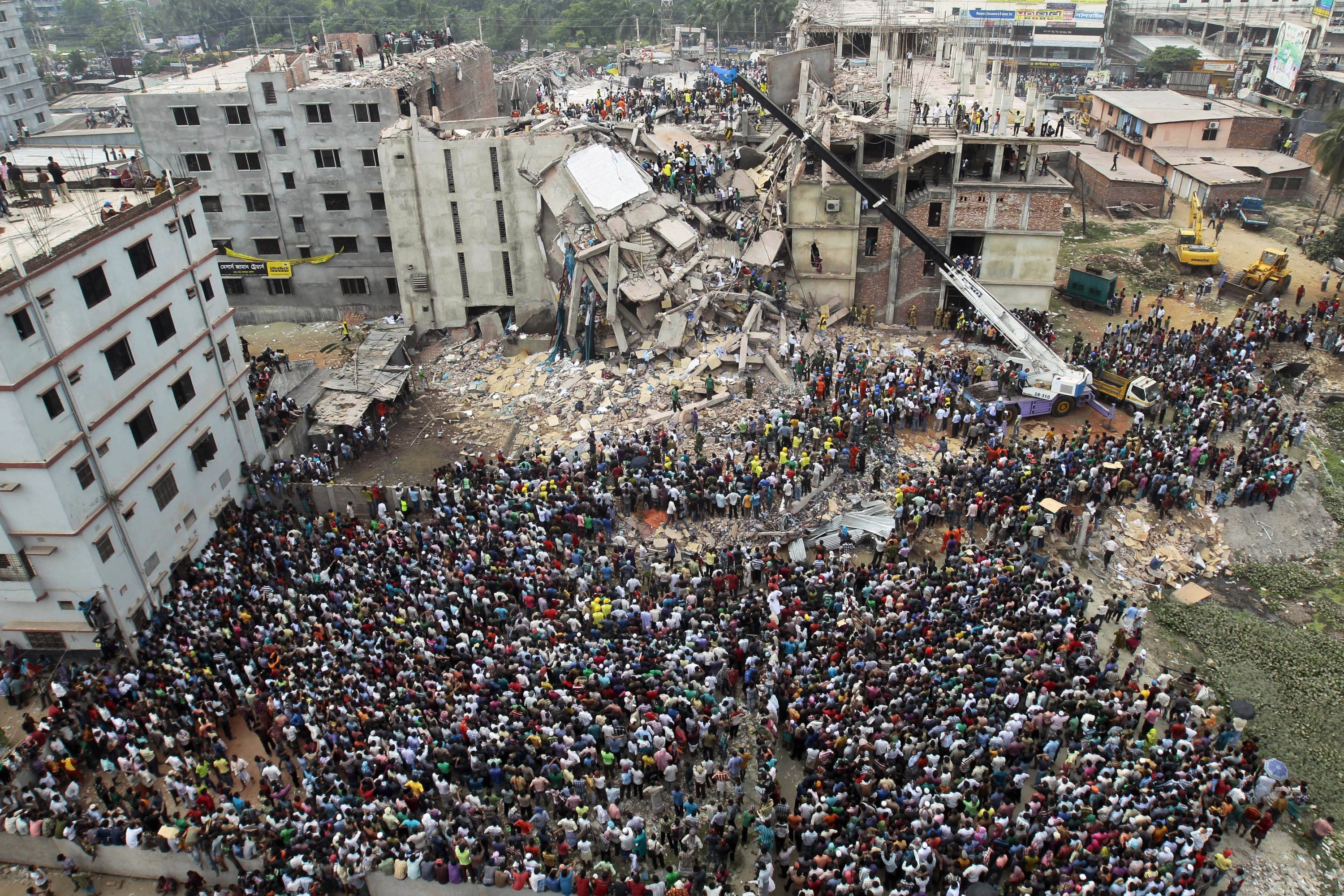 In this April 25, 2013, file photo, Bangladeshi people gather as rescuers look for survivors and victims at the site of the Rana Plaza building that collapsed a day earlier, in Savar, near Dhaka, Bangladesh. (AP Photo)