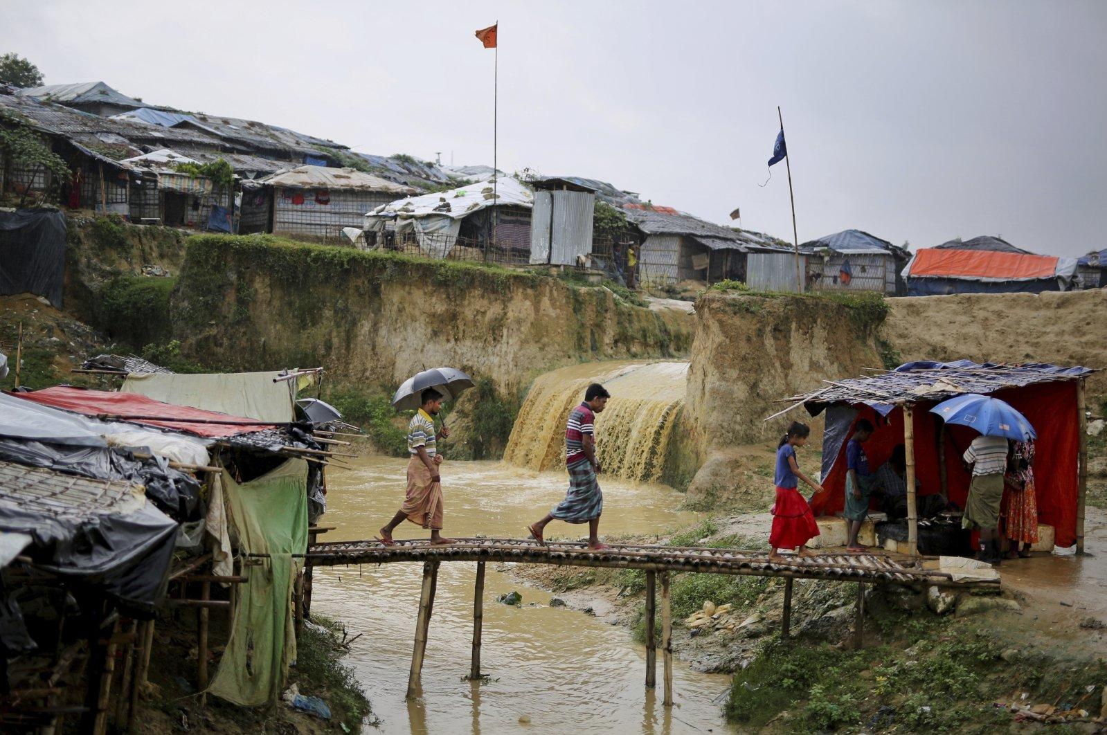 Sewer water flows in the back as Rohingya refugees cross a makeshift bamboo bridge at Kutupalong refugee camp, Bangladesh, Aug. 28, 2018. (AP Photo)