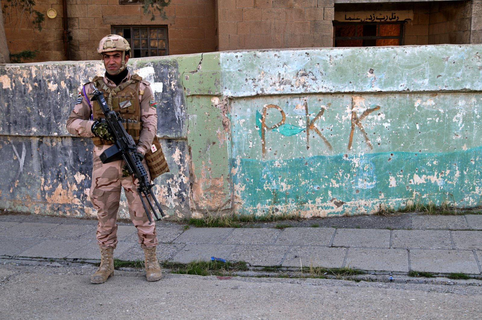 An Iraqi army soldier stands next to the graffiti left by PKK terrorists, who recently withdrew in Sinjar, Iraq. Dec. 4, 2020. (AP File Photo)