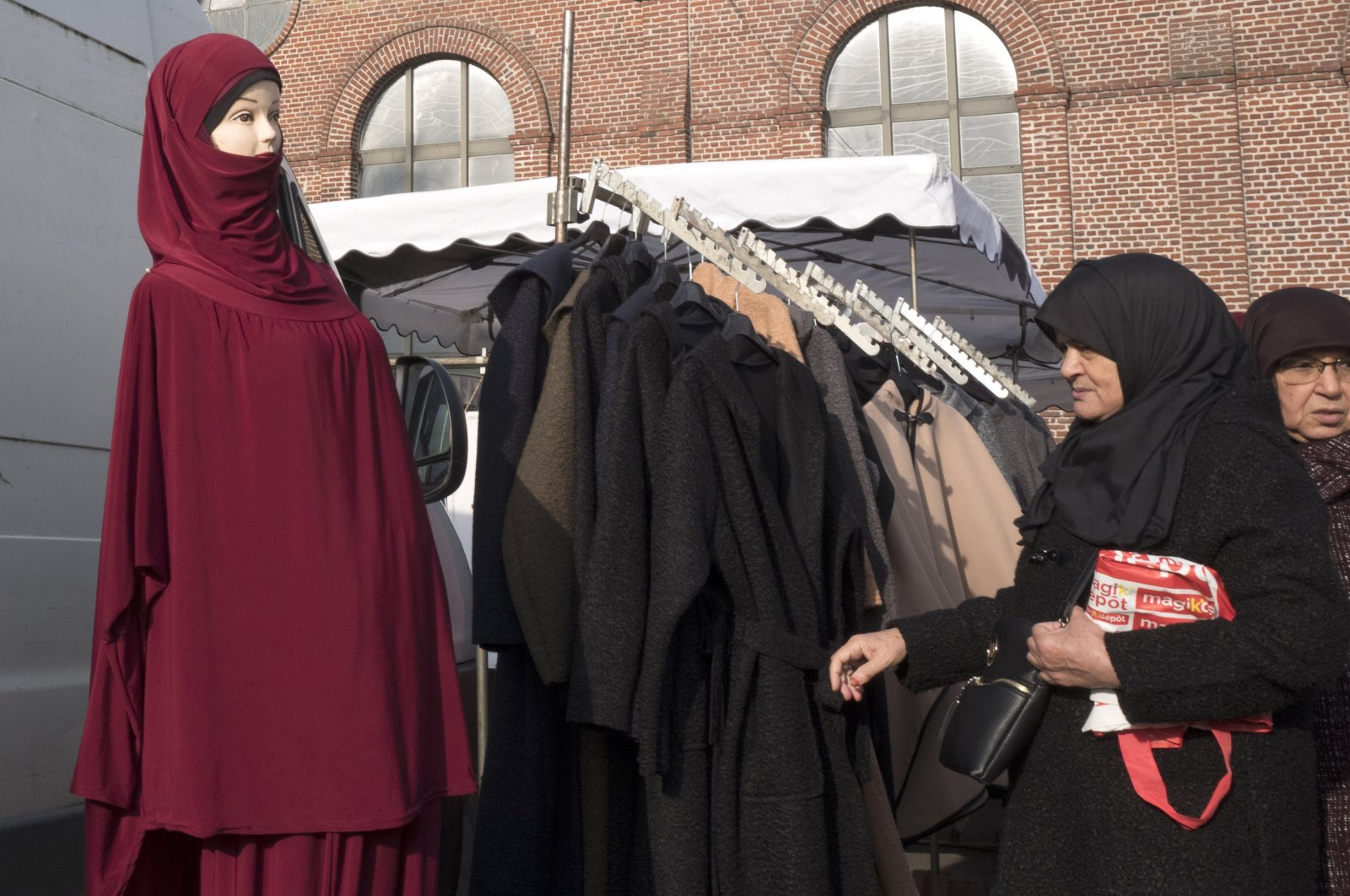 Women walk past a mannequin presenting Muslim fashion at an open-air market in Lille, northern France, Oct. 31, 2019. (AP Photo)